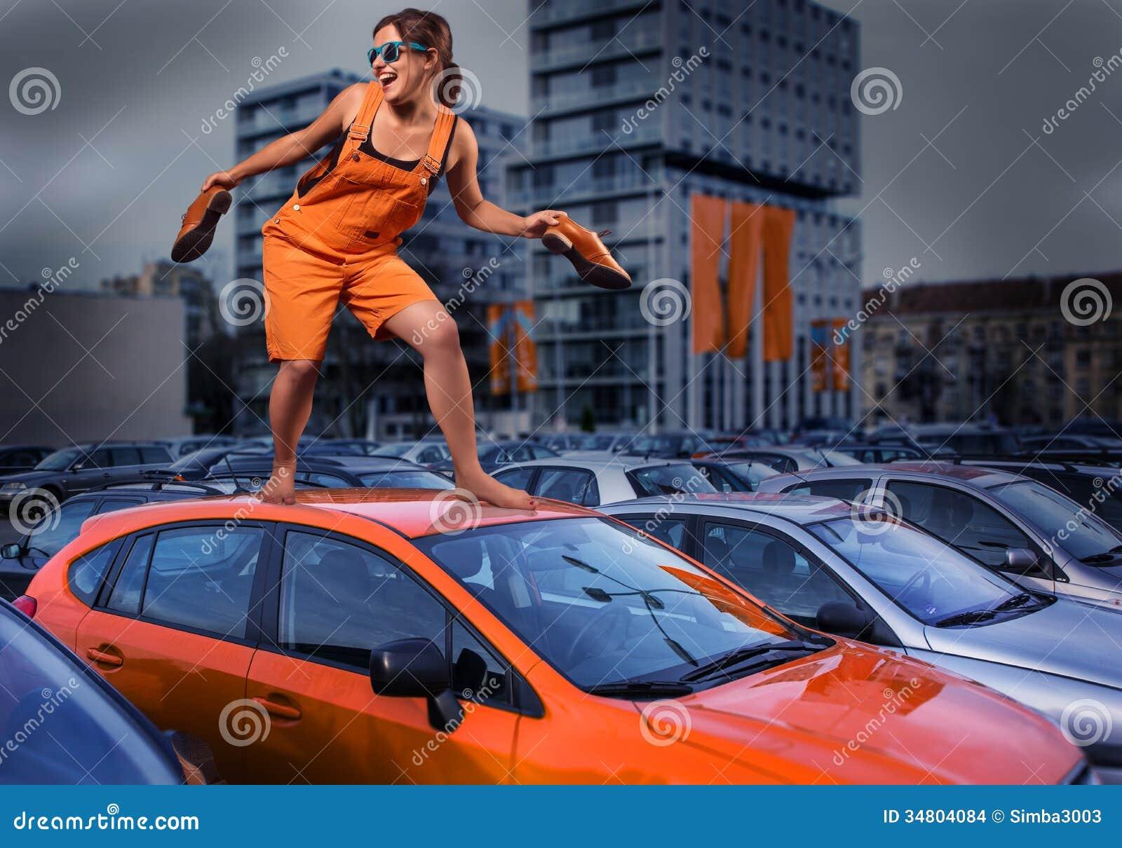 Εύθυμο μοντέρνο κορίτσι στις πορτοκαλιές φόρμες που στέκονται στη στέγη αυτοκινήτων στο χώρο στάθμευσης
