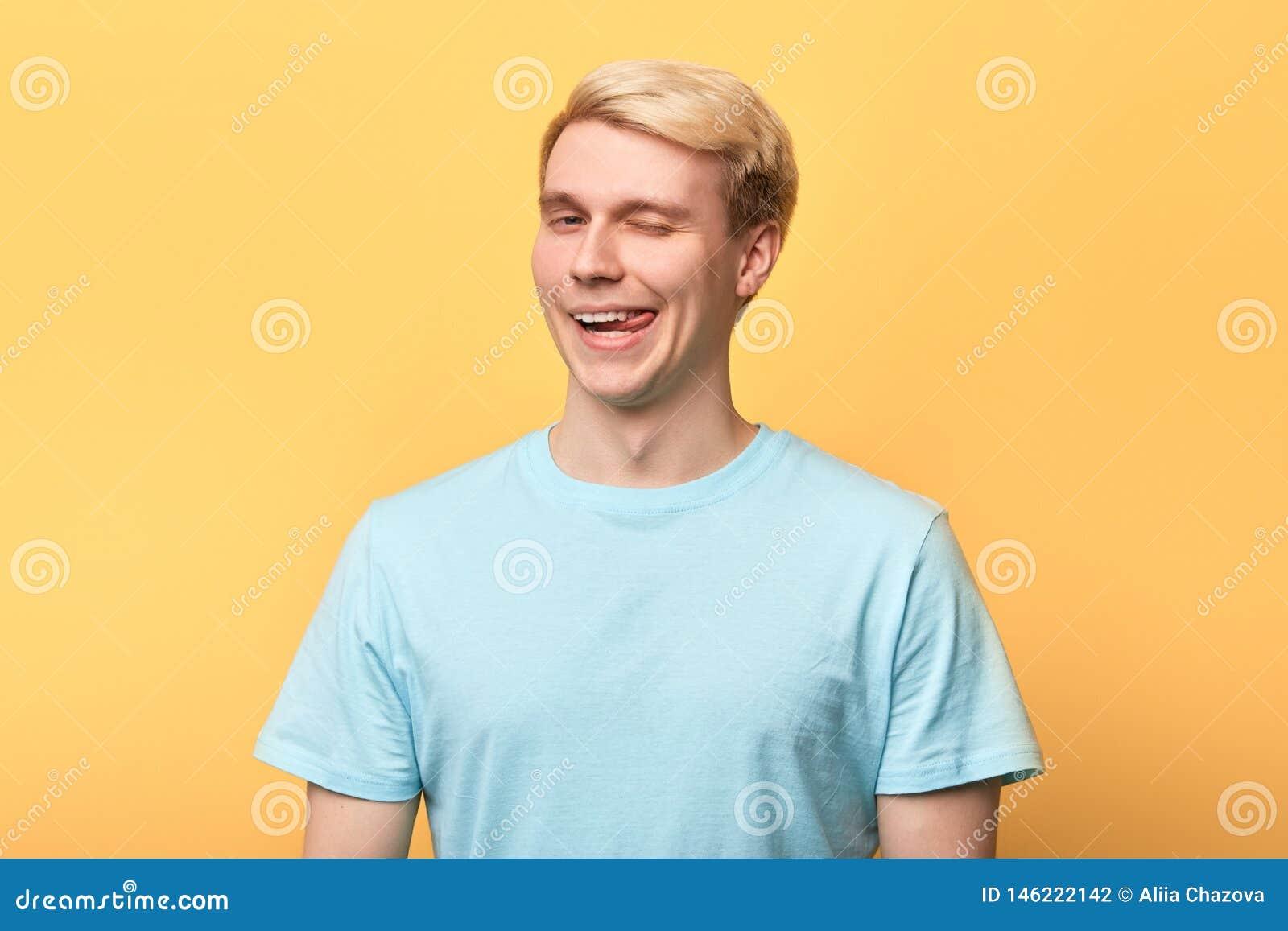 Εύθυμο νέο αστείο άτομο που βάζει έξω τη γλώσσα και το κλείσιμο του ματιού του