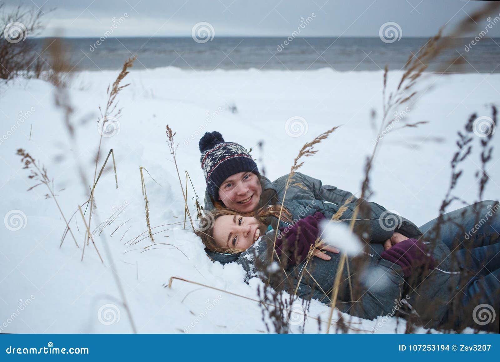 Εύθυμο νέο ζεύγος που βρίσκεται στο χιόνι κοντά στην παραλία SE Χειμερινές romanctic διακοπές