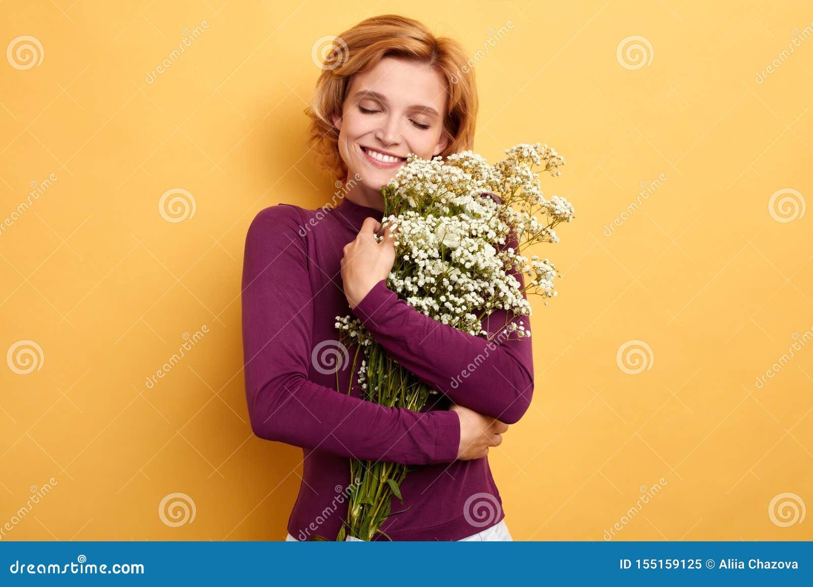 Εύθυμο ξανθό αγκάλιασμα γυναικών, που αγκαλιάζει τα λουλούδια