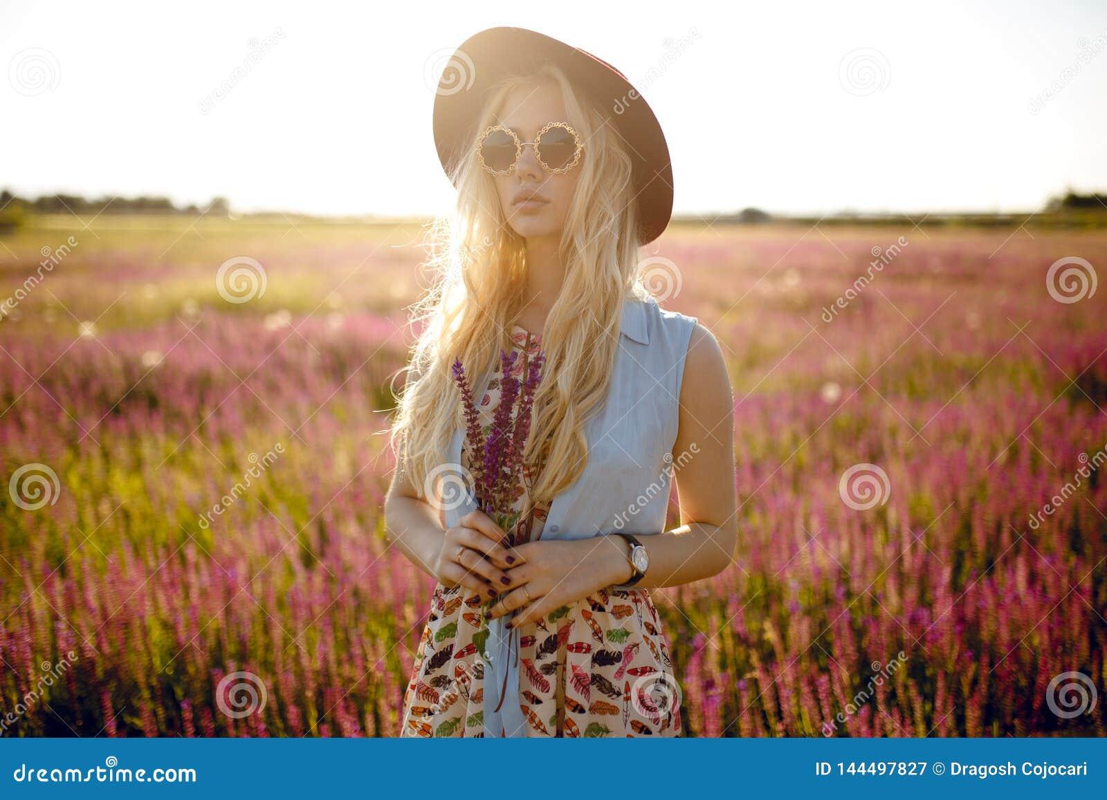 Εύθυμο ξανθό κορίτσι που φορά στο καπέλο και τα στρογγυλά γυαλιά ηλίου, που κάθονται σε έναν floral τομέα, πίσω από το όμορφο υπό