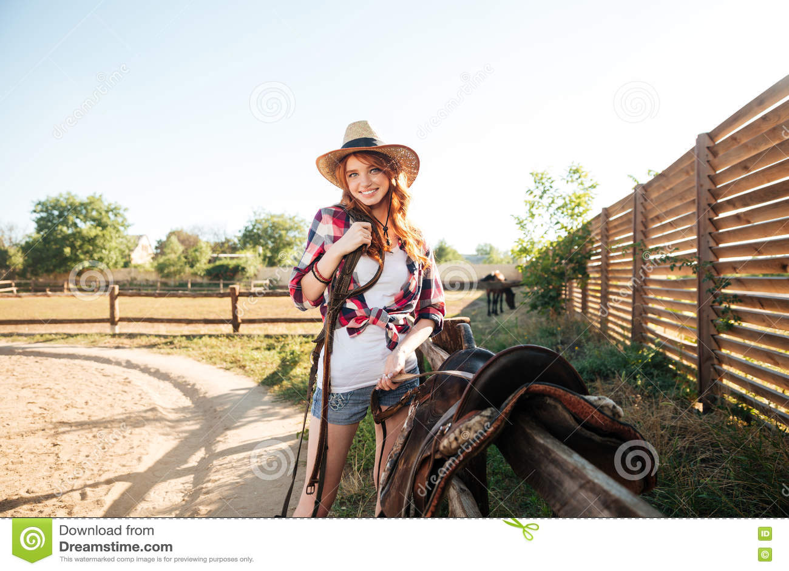 Εύθυμο χαμόγελο cowgirl προετοιμάζοντας τη σέλα αλόγων για έναν γύρο