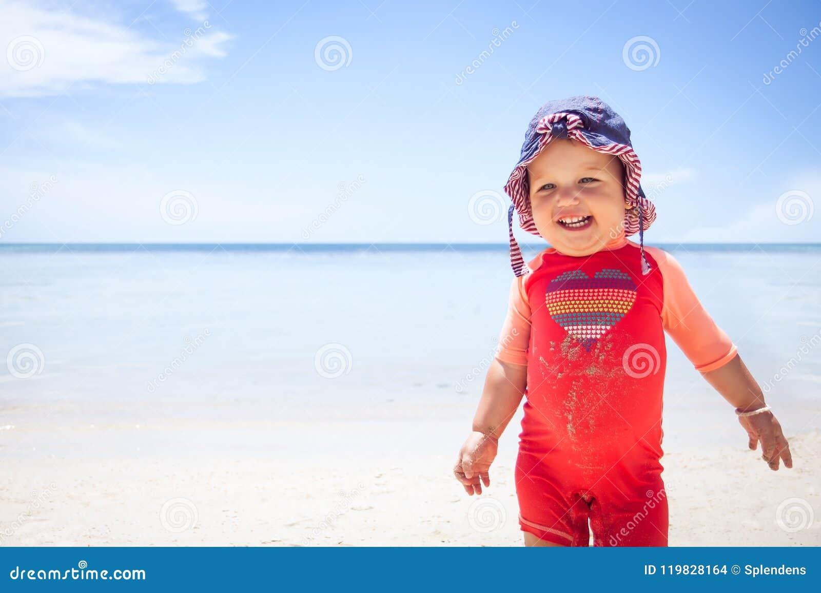 Εύθυμο χαριτωμένο ευτυχές sunscreen ουρανού θάλασσας παραλιών κοστουμιών ήλιων παιδιών μωρών χαμόγελου προστατευτικό μπλε διάστημ