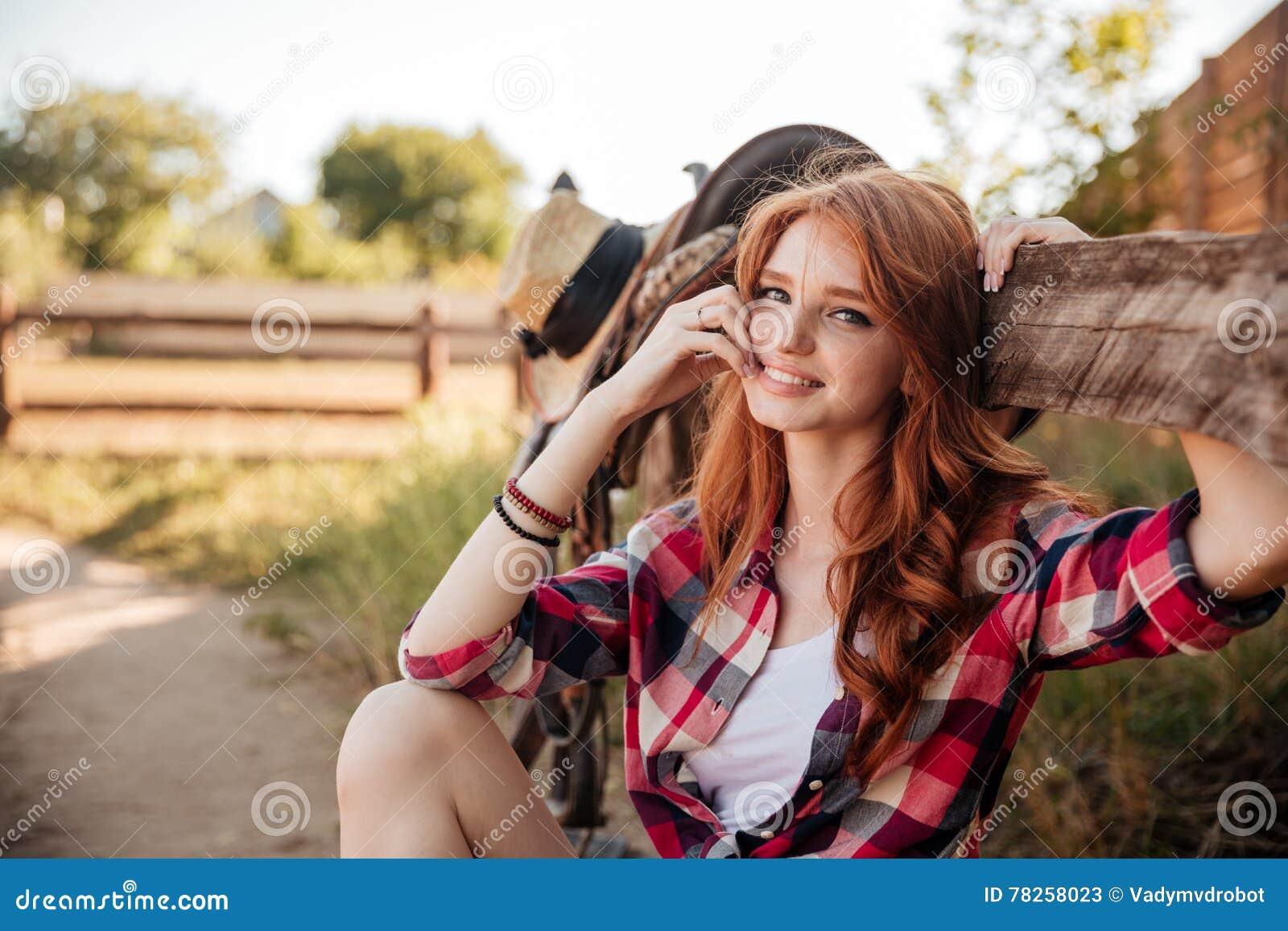 Εύθυμο χαριτωμένο redhead cowgirl που στηρίζεται στο φράκτη αγροκτημάτων