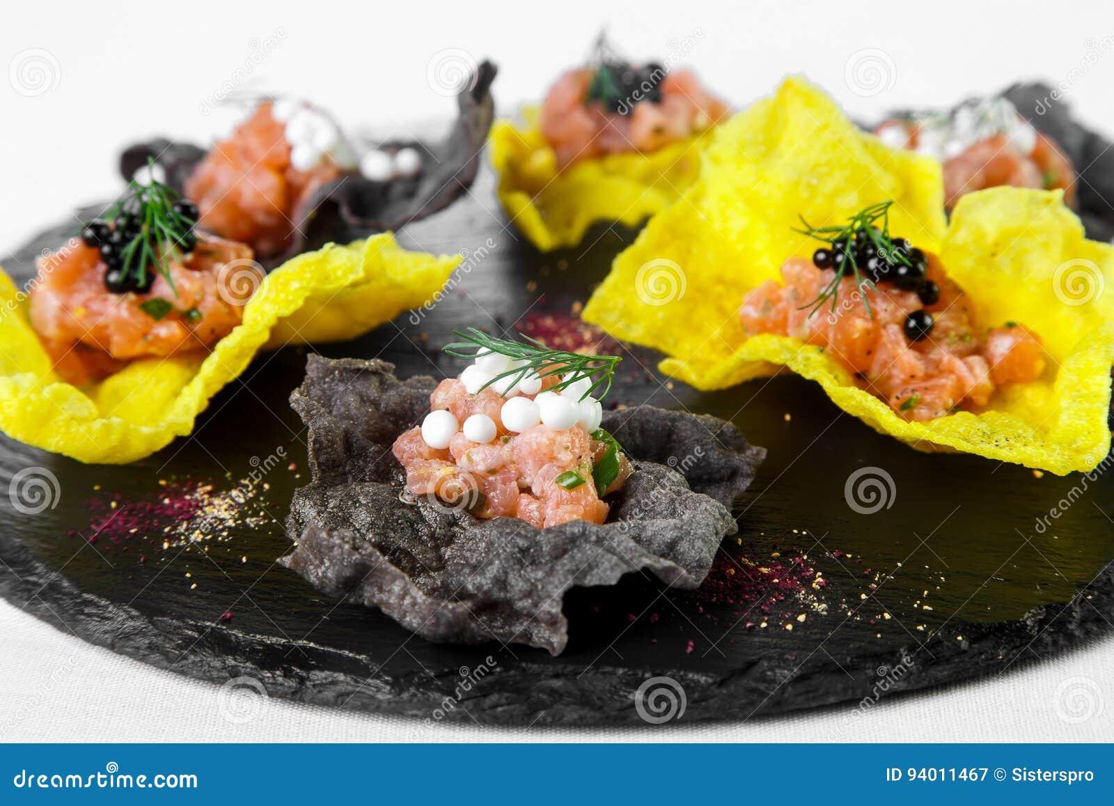 Ελαφρύ πρόχειρο φαγητό των μαύρων και κίτρινων τσιπ που γεμίζουν με τα θαλασσινά στο sto