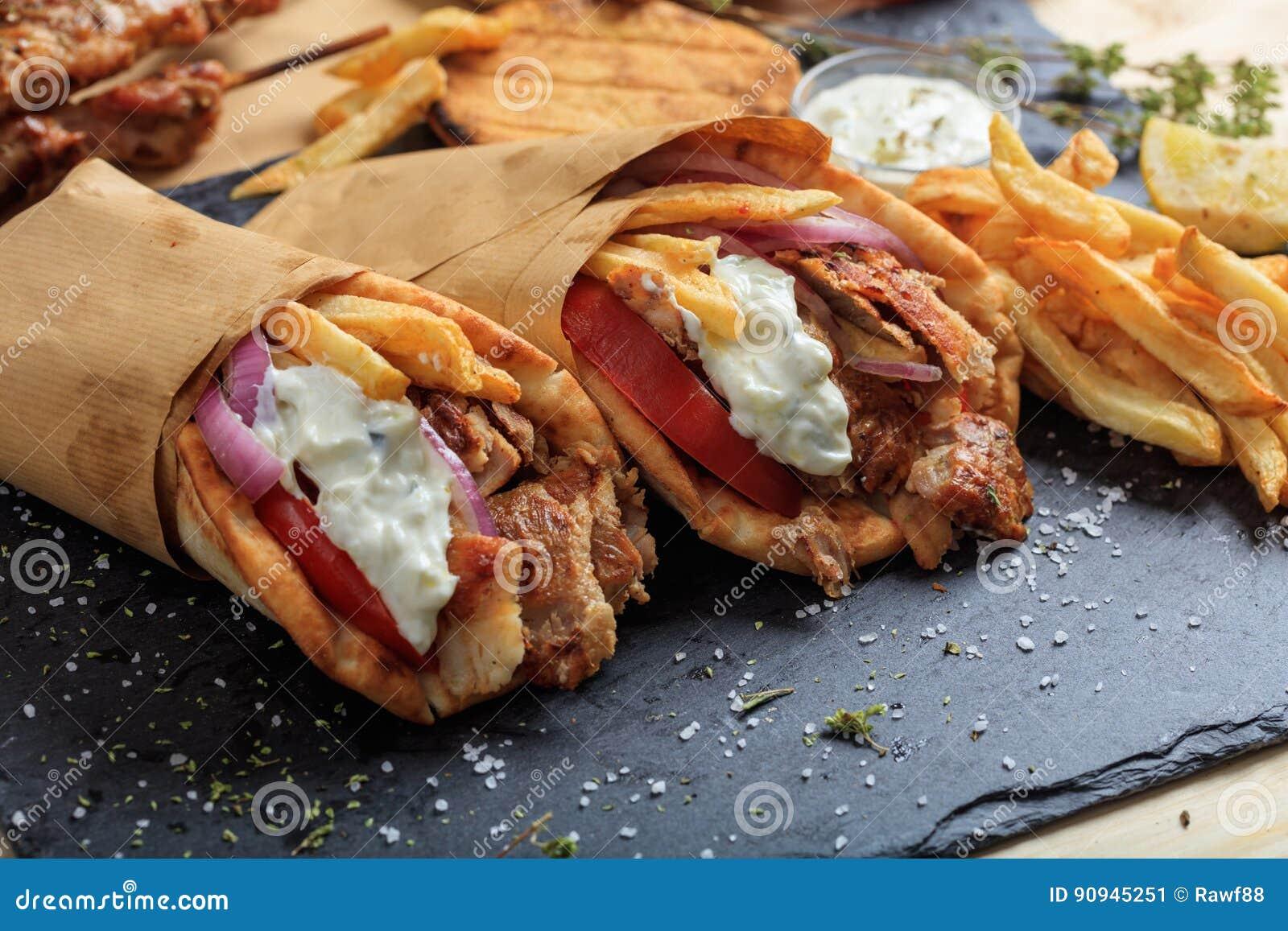Ελληνικά γυροσκόπια που τυλίγονται στα ψωμιά pita σε ένα μαύρο πιάτο