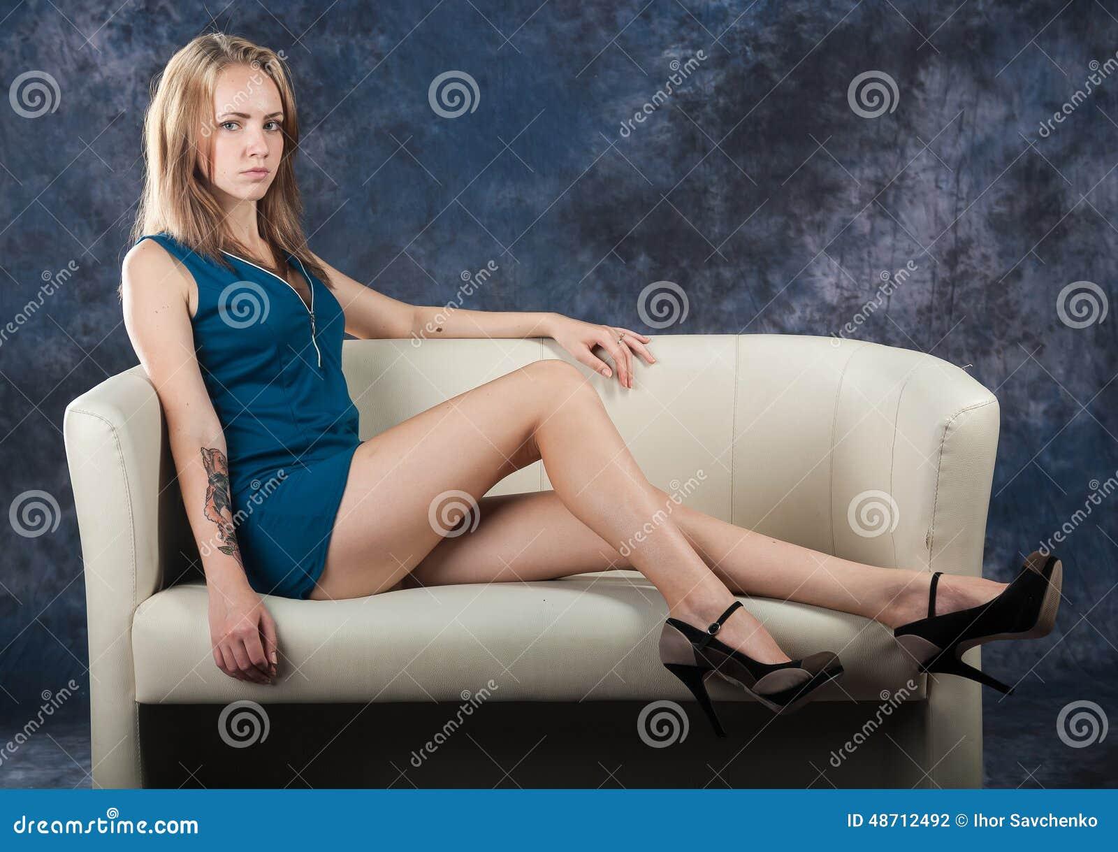 Ελκυστική λεπτή συνεδρίαση κοριτσιών στο ντιβάνι