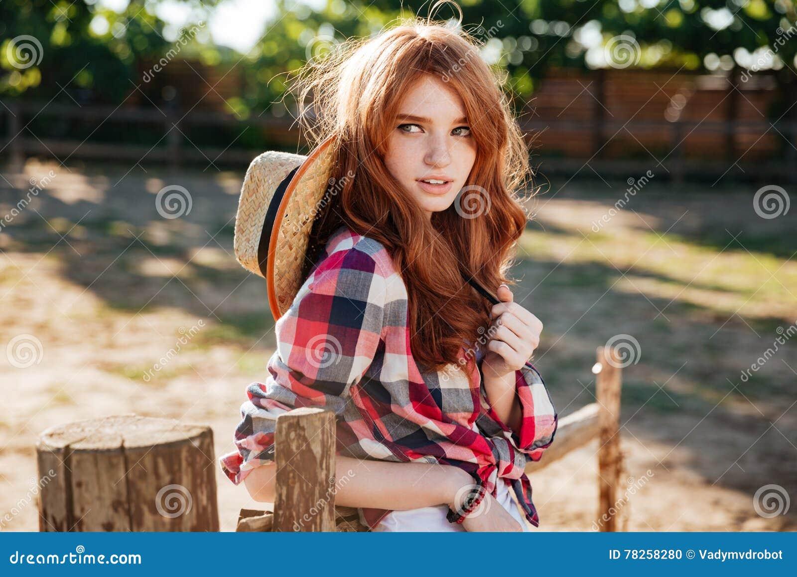 Ελκυστική redhead νέα γυναίκα cowgirl που στέκεται υπαίθρια