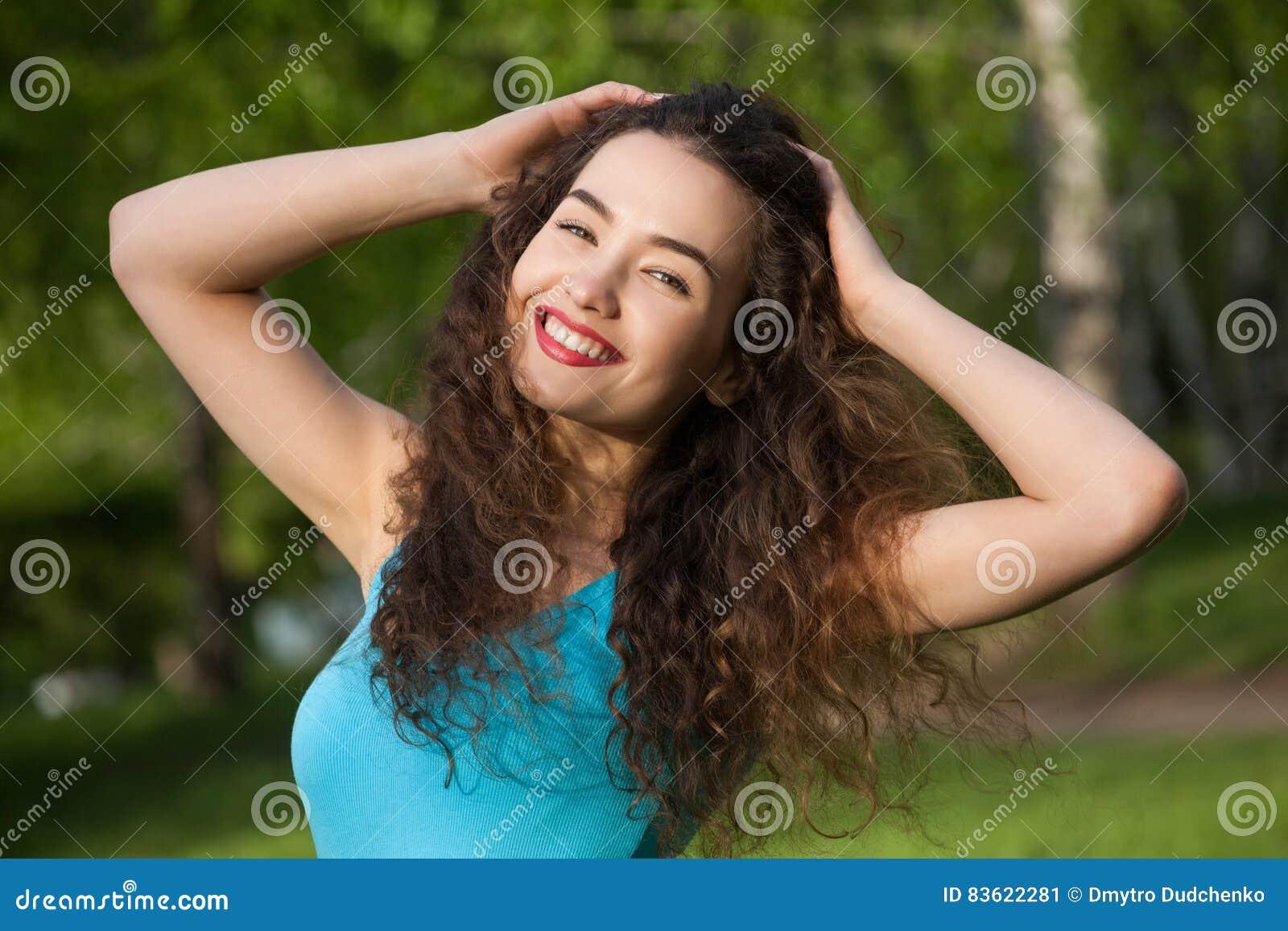 Ελκυστικός, νέο κορίτσι με σγουρός, μακρυμάλλης, χαμογελώντας και κάνοντας selfie