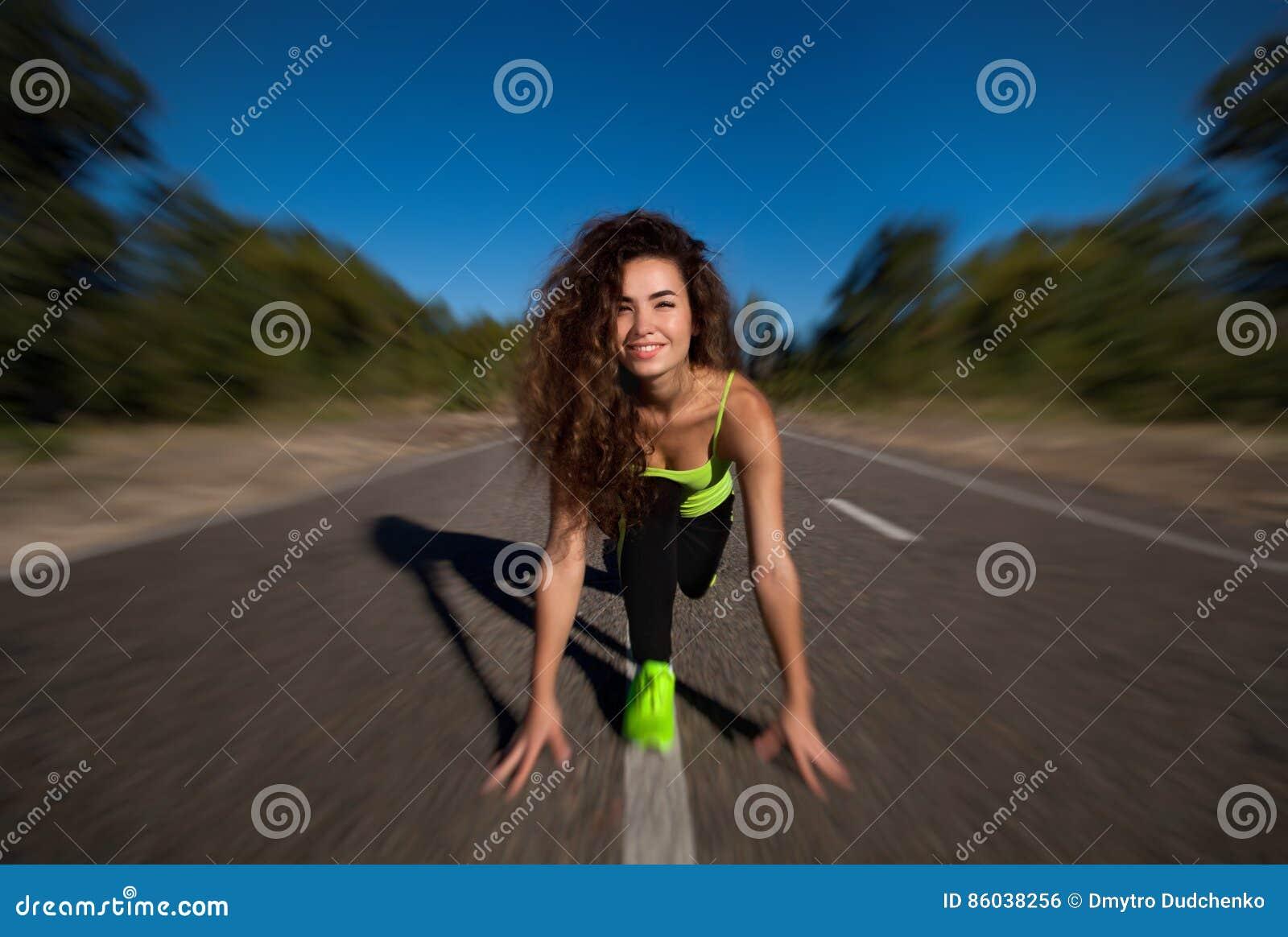 Ελκυστικός σγουρός αθλητής κοριτσιών που κάνει τις ασκήσεις πρωινού έξω