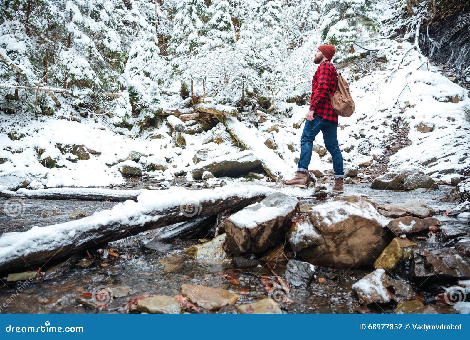 Ελκυστικό γενειοφόρο άτομο που στέκεται κοντά στον ποταμό στο χειμερινό δάσος