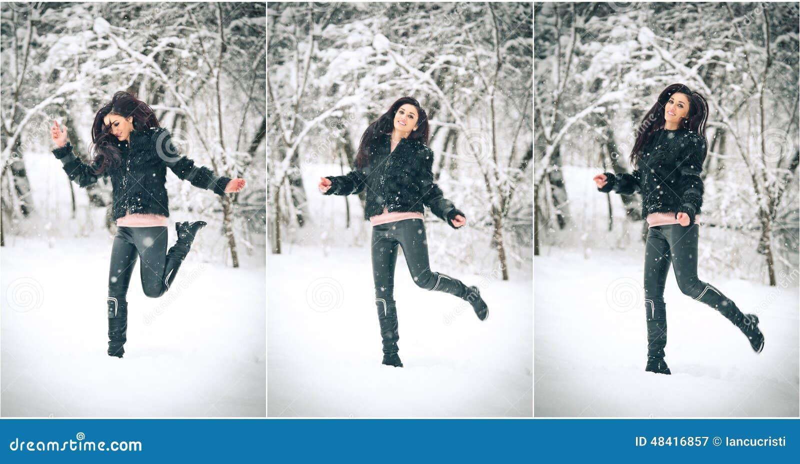 Ελκυστικό κορίτσι brunette στη μαύρη τοποθέτηση που παίζει στο χειμερινό τοπίο Όμορφη νέα γυναίκα με μακρυμάλλη απολαμβάνοντας το