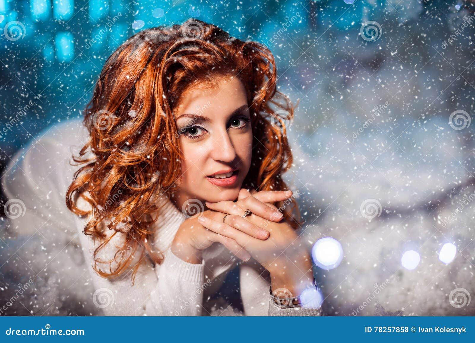 Ελκυστικό κόκκινο επικεφαλής κορίτσι που γονατίζει και σε τα τέσσερα μεταξύ snowdrift
