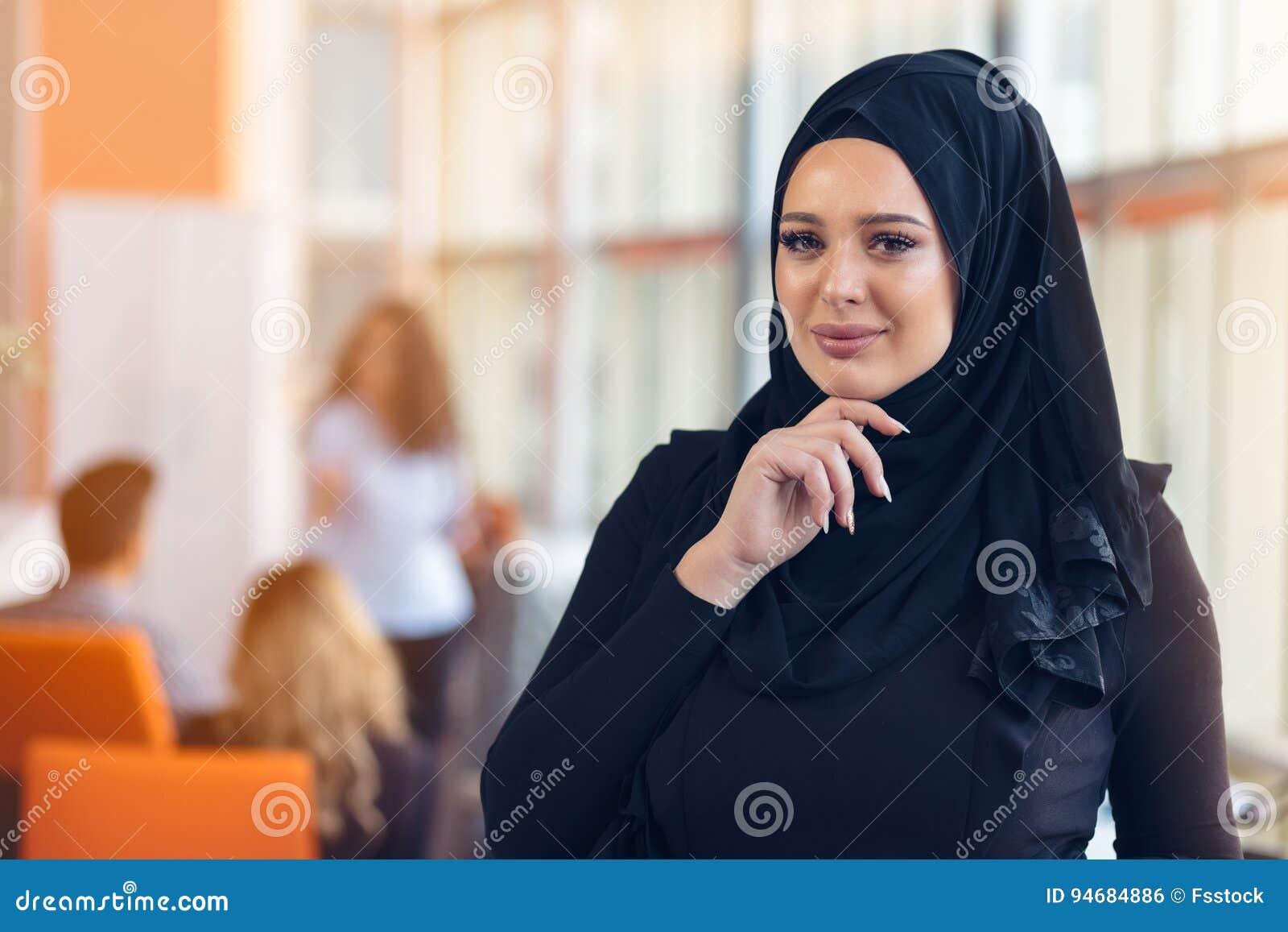 Ελκυστικό πορτρέτο της νέας μουσουλμανικής γυναίκας με το μαύρο hijab στο γραφείο