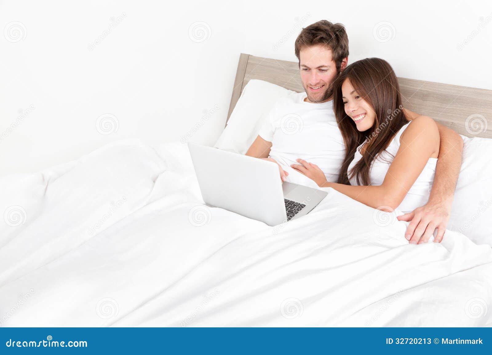 Ζεύγος κρεβατιών ευτυχές στο φορητό προσωπικό υπολογιστή στο δωμάτιο κρεβατιών