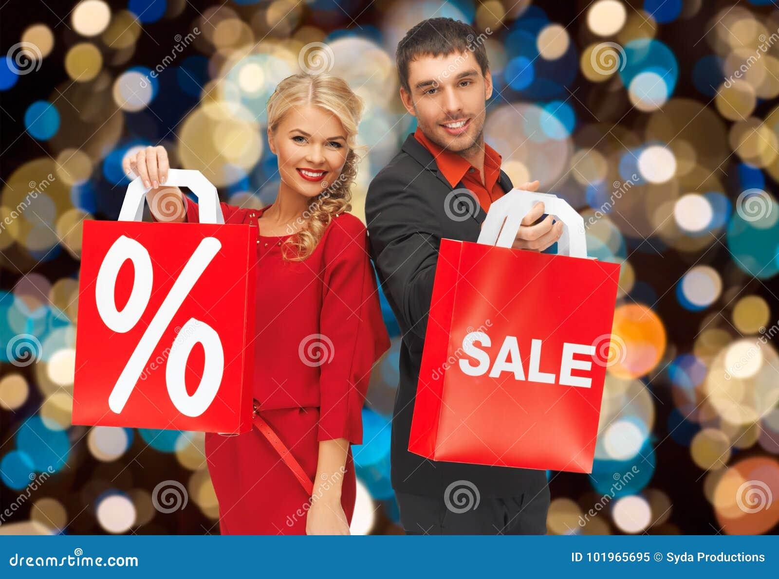 Ζεύγος με το σημάδι πώλησης και έκπτωσης στην τσάντα αγορών