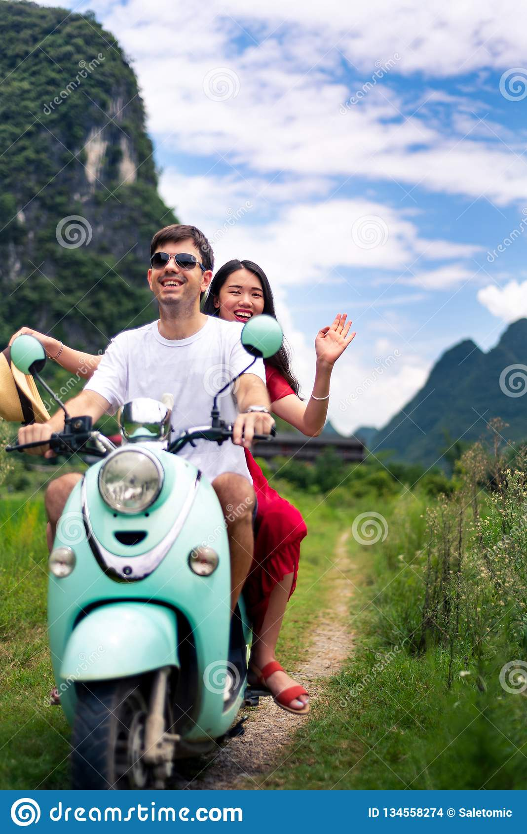 Ζεύγος που έχει τη διασκέδαση στη μοτοσικλέτα γύρω από τους τομείς ρυζιού στην Κίνα
