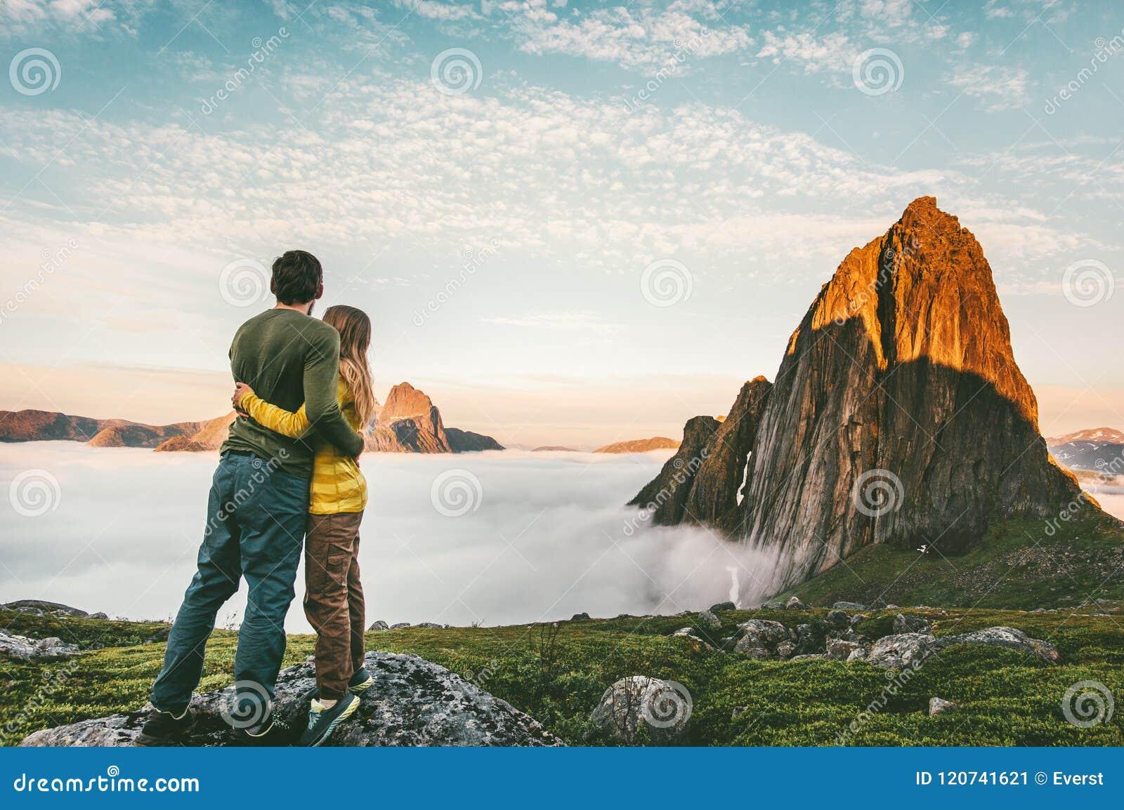 Ζεύγος που αγκαλιάζει απολαμβάνοντας την οικογένεια τοπίων βουνών που ταξιδεύει από κοινού