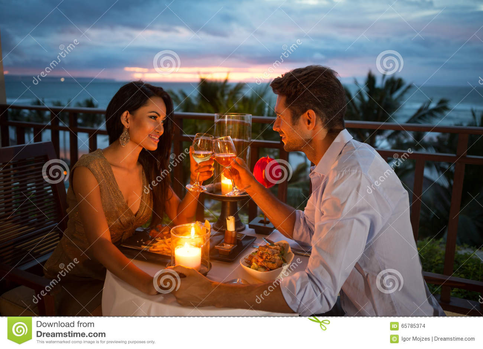Ζεύγος που απολαμβάνεται ένα ρομαντικό γεύμα από το φως ιστιοφόρου