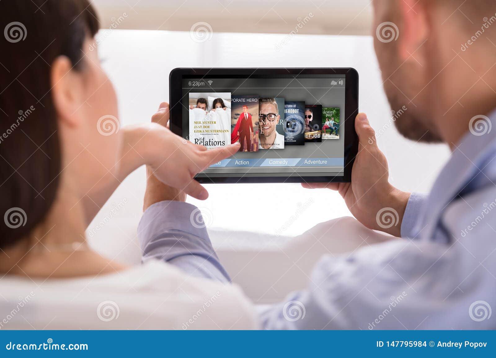 Ζεύγος που επιλέγει τους σε απευθείας σύνδεση κινηματογράφους στην ψηφιακή ταμπλέτα