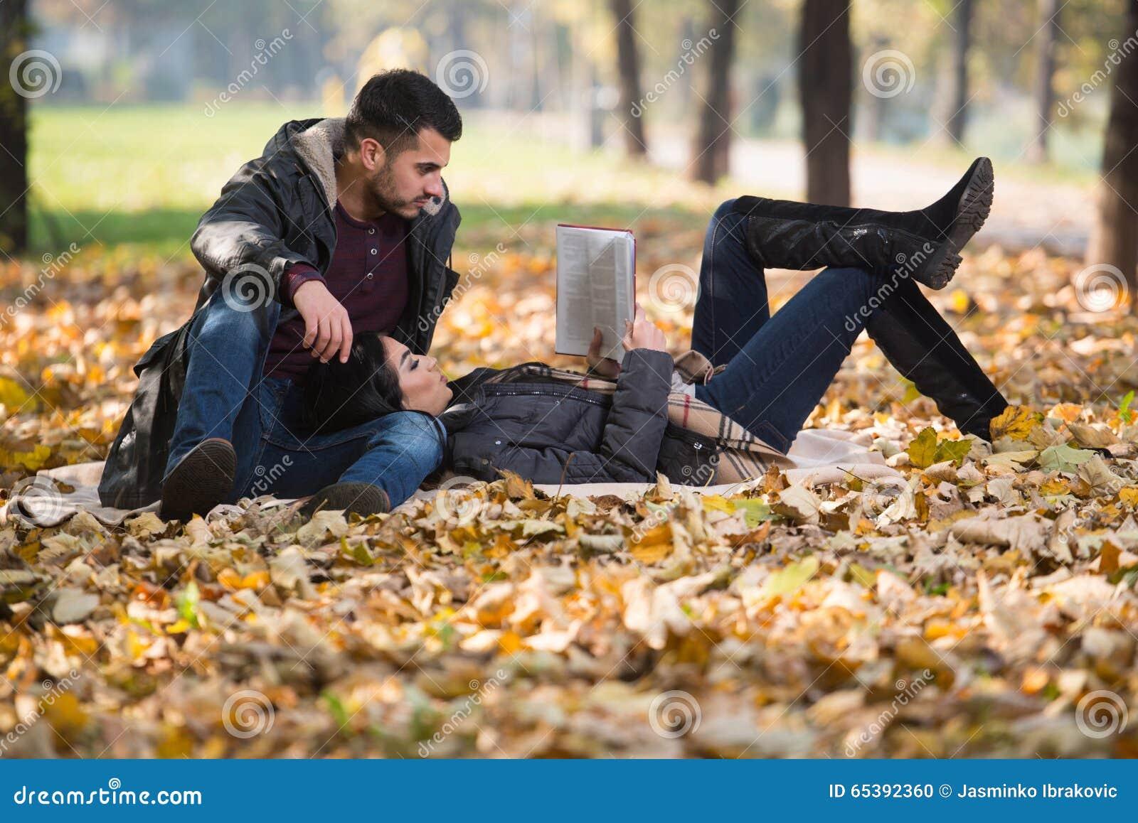 Ζεύγος που διαβάζει ένα βιβλίο κατά τη διάρκεια του φθινοπώρου