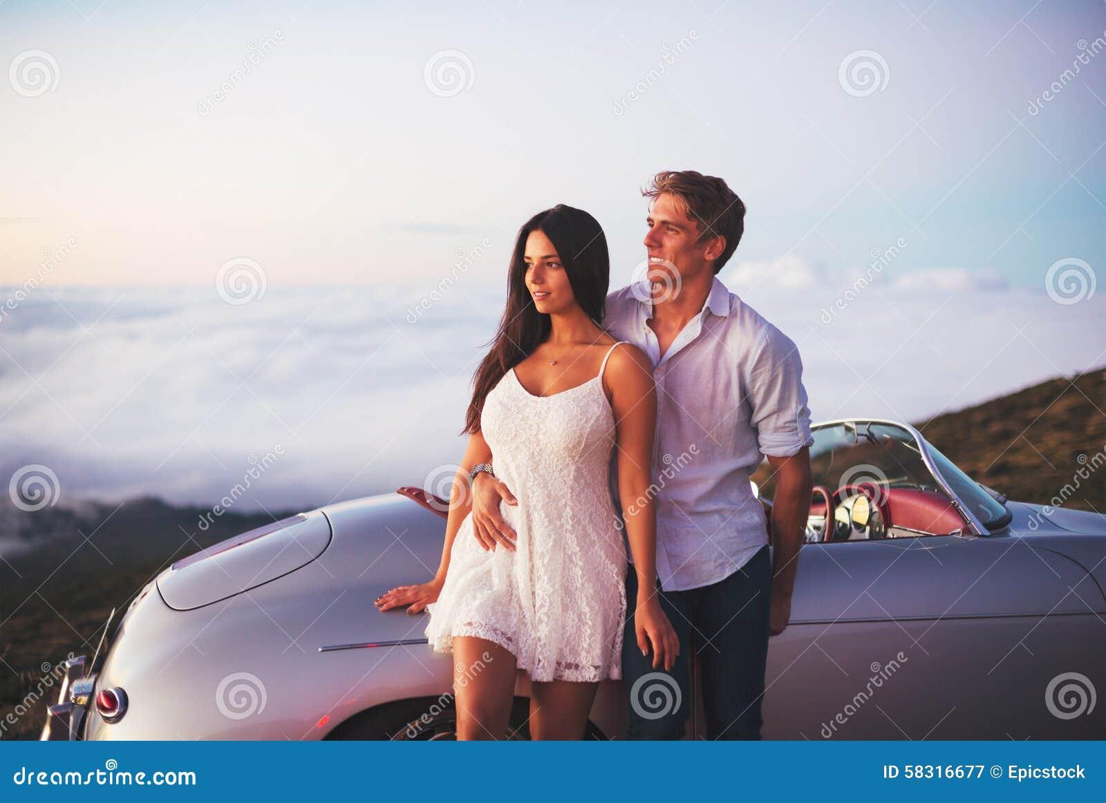 Ζεύγος που προσέχει το ηλιοβασίλεμα με το κλασικό εκλεκτής ποιότητας αυτοκίνητο