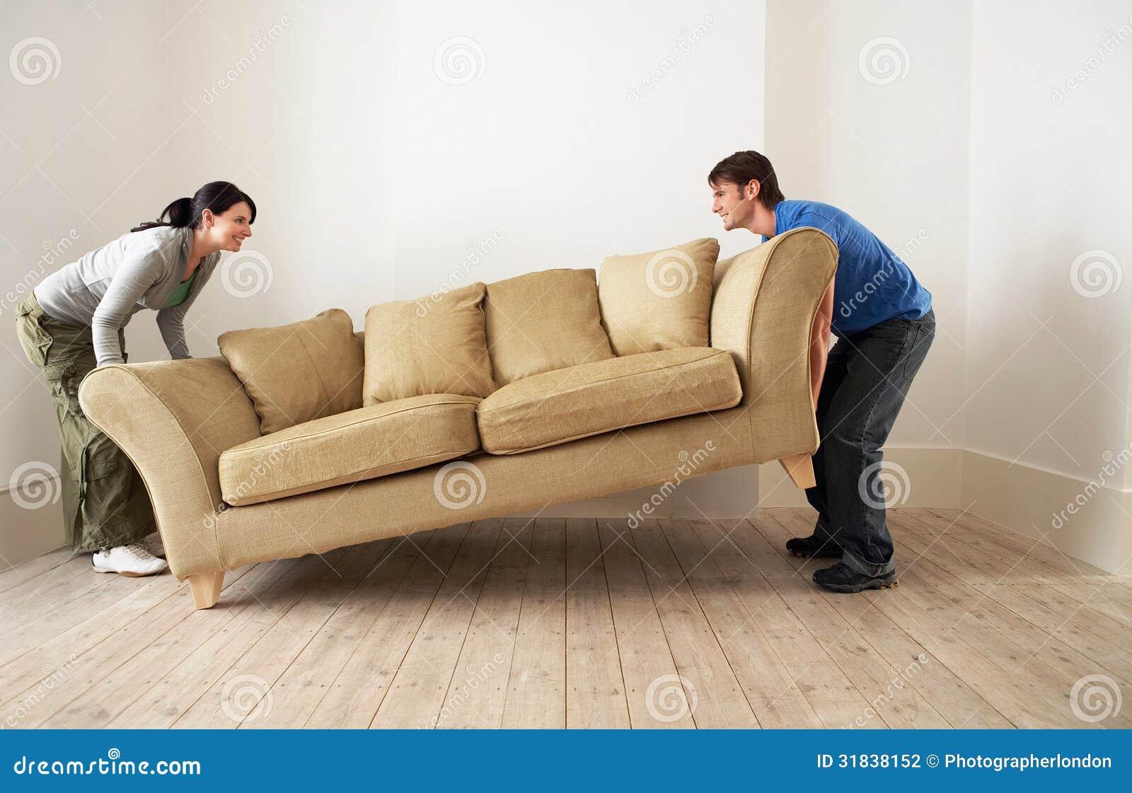 Ζεύγος που τοποθετεί τον καναπέ στο καθιστικό του νέου σπιτιού