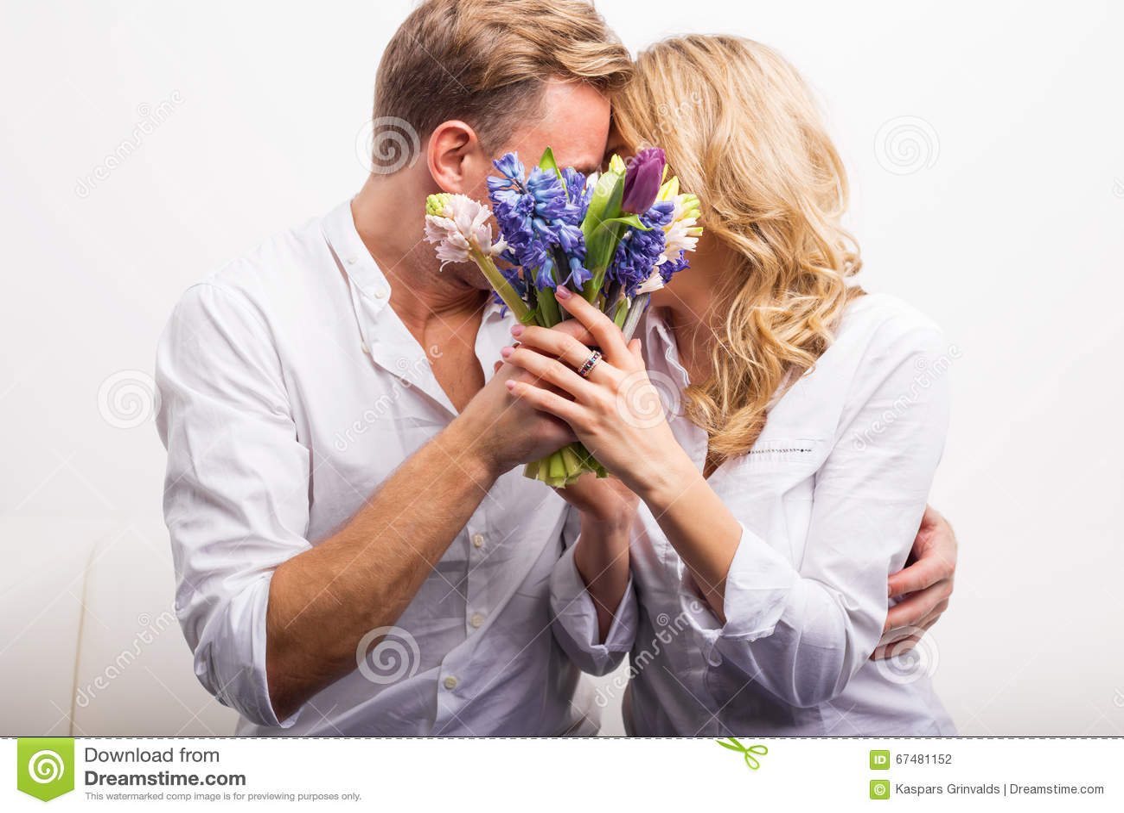 Ζεύγος που φιλά και που κρατά τα λουλούδια για να κρύψει