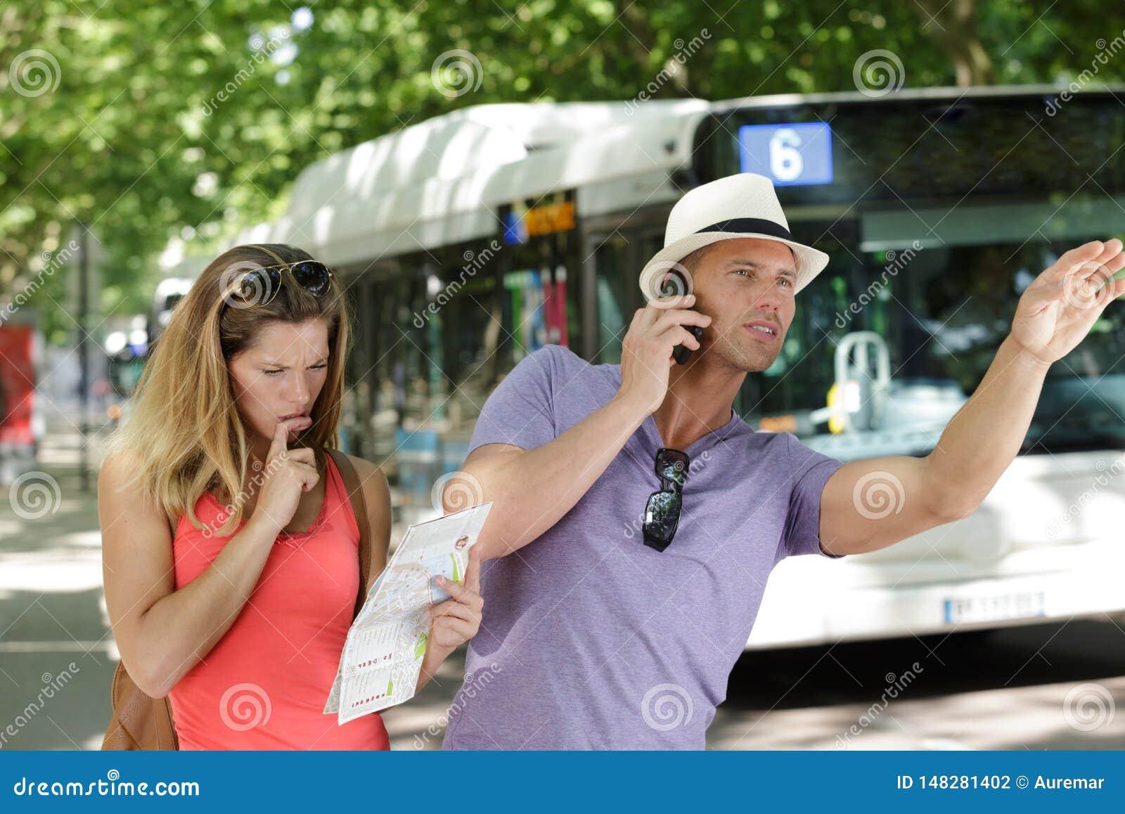 Ζεύγος στα προάστια που κρατούν το χάρτη και που χαιρετούν το λεωφορείο