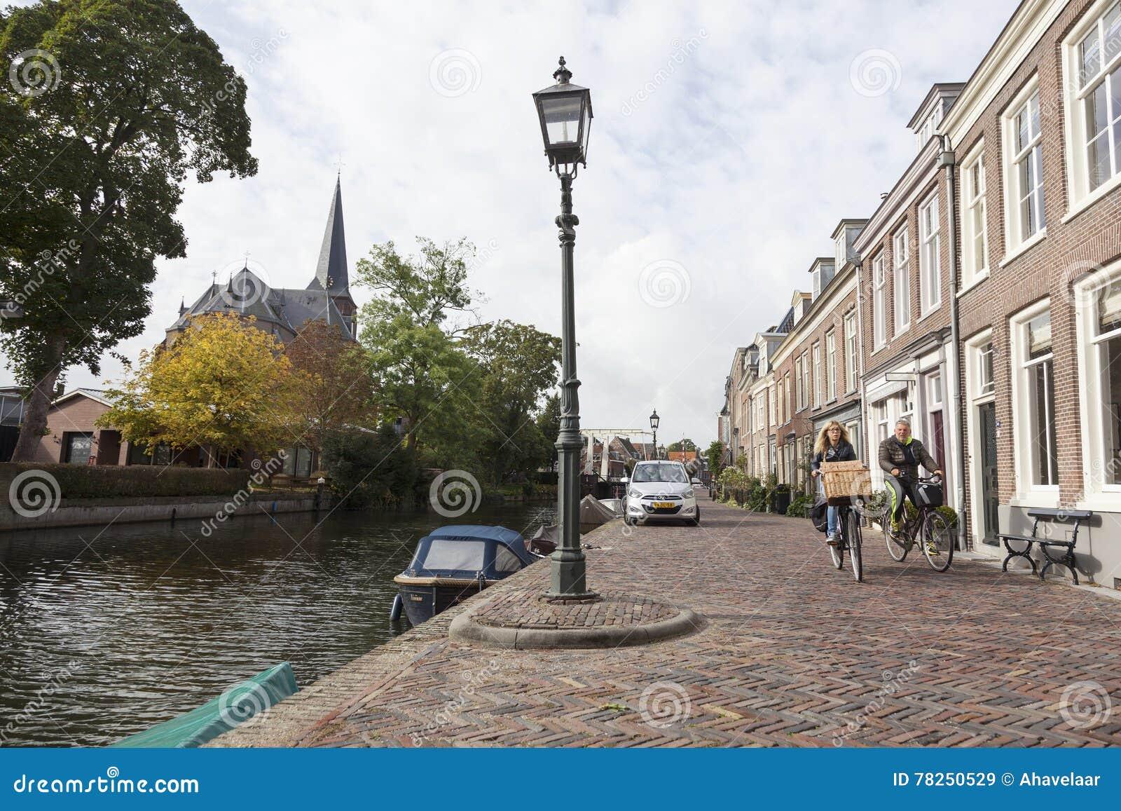 Ζεύγος στο ποδήλατο στο ανάχωμα του ποταμού Vecht στο ολλανδικό vill