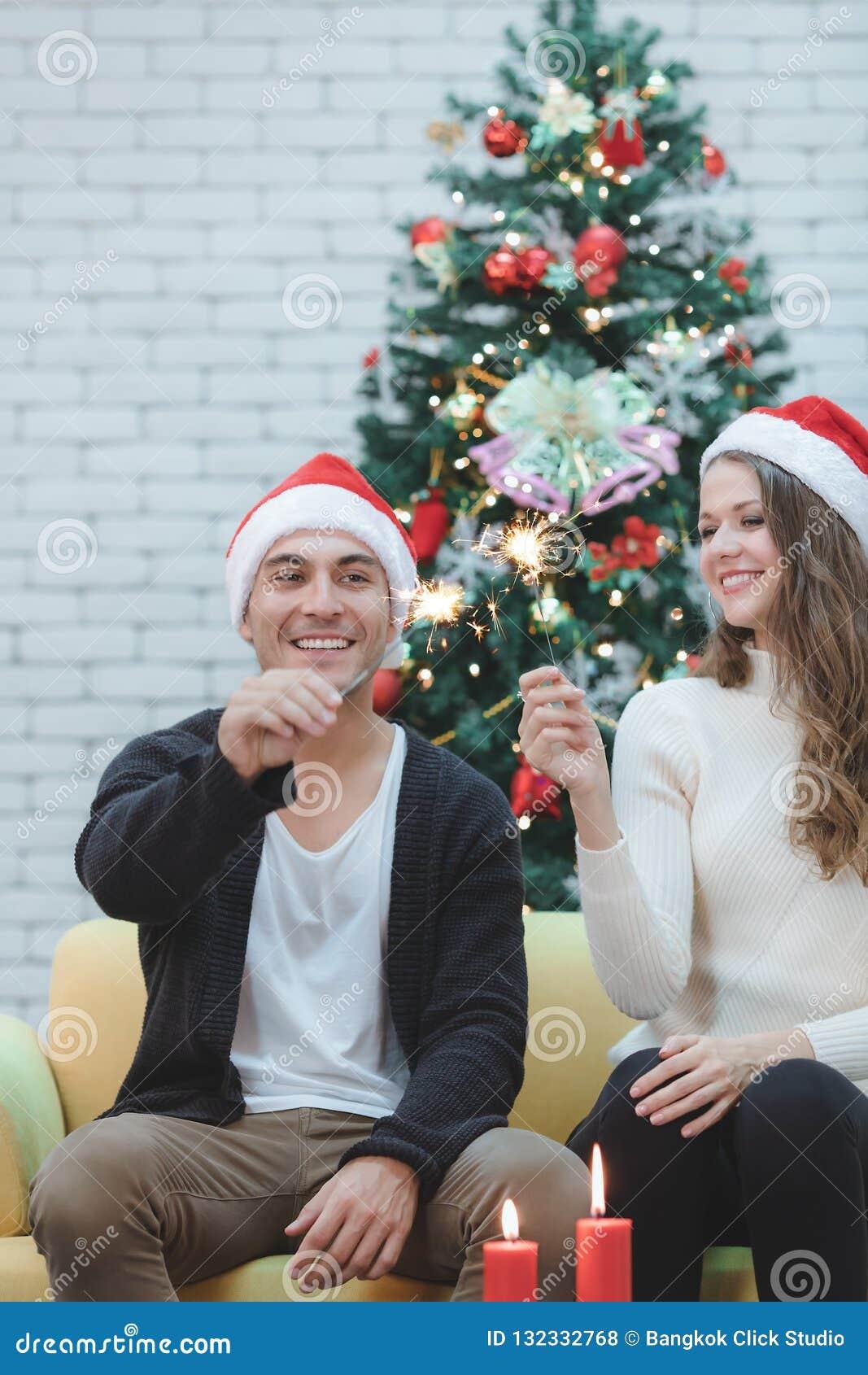 Ζεύγος Youn στην κόκκινη συνεδρίαση καπέλων στον καναπέ μεταξύ των χριστουγεννιάτικων δέντρων α