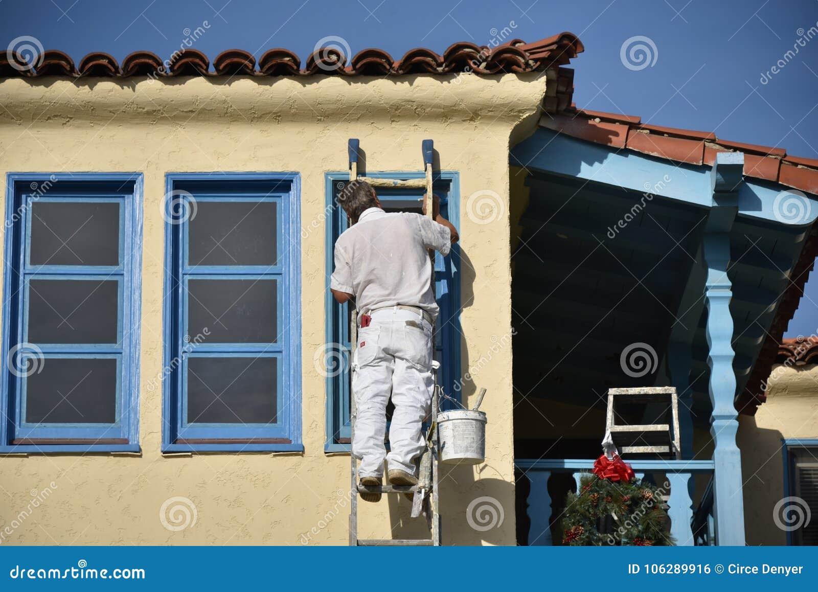 Ζωγράφος, που χρωματίζει ένα κίτρινο και μπλε τακτοποιημένο σπίτι