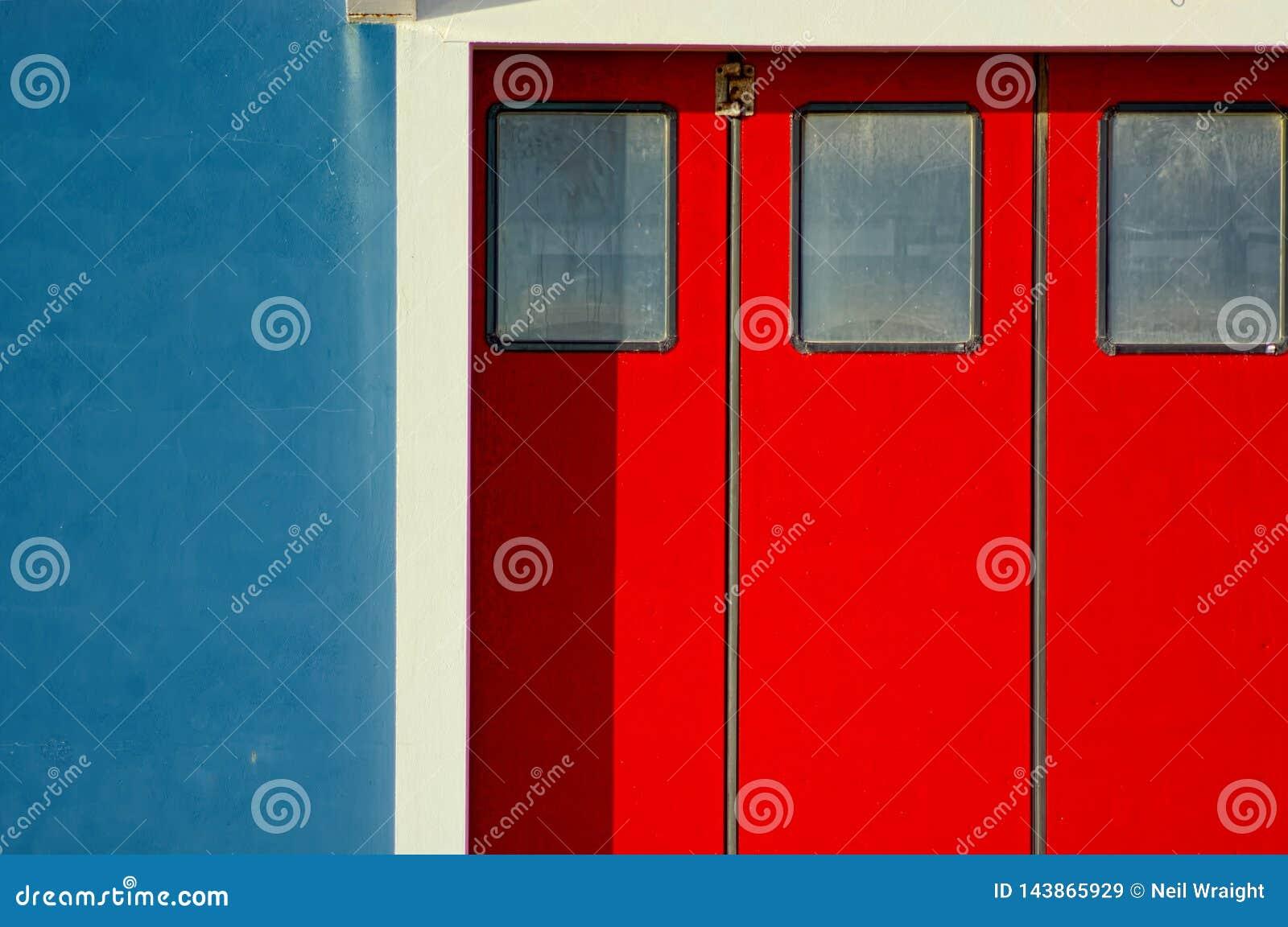 Ζωηρές κόκκινες πόρτες, μπλε τοίχος, άσπρη περιποίηση αφηρημένο χρώμα