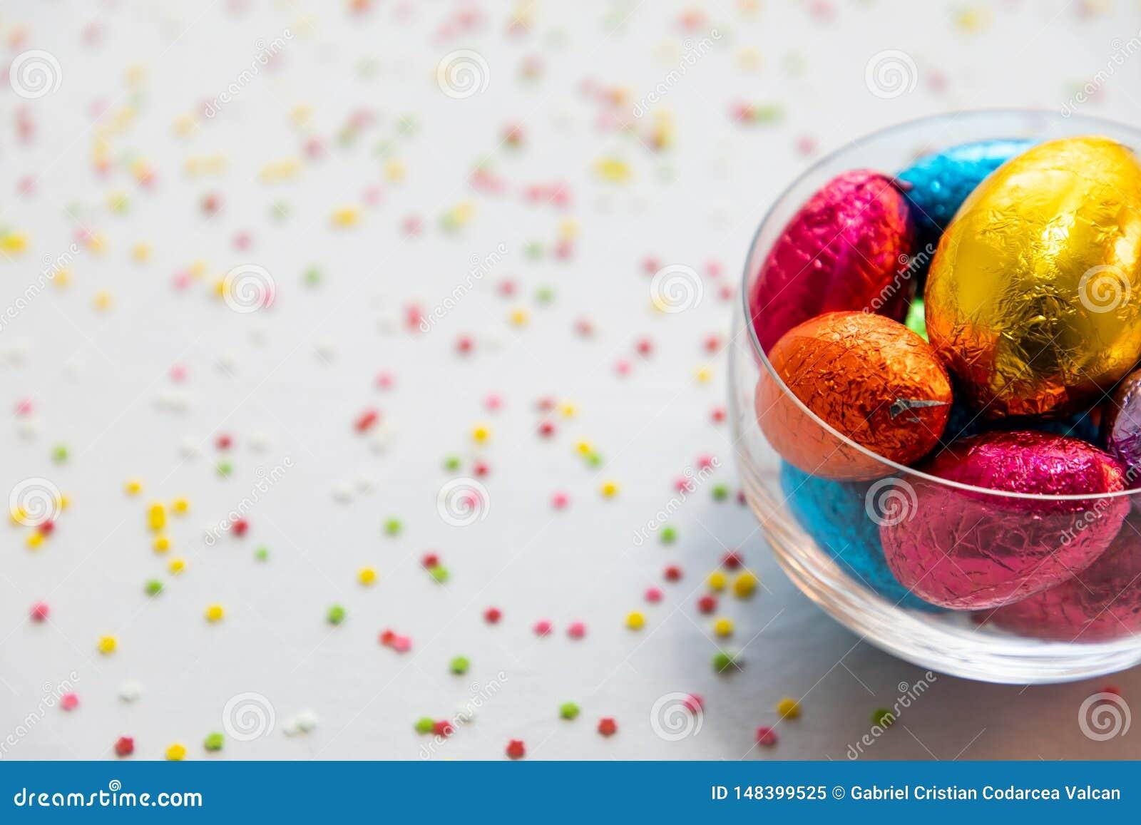 Ζωηρόχρωμα αυγά Πάσχας σοκολάτας σε ένα διαφανές κύπελλο με το άσπρο υπόβαθρο και το θολωμένο κομφετί