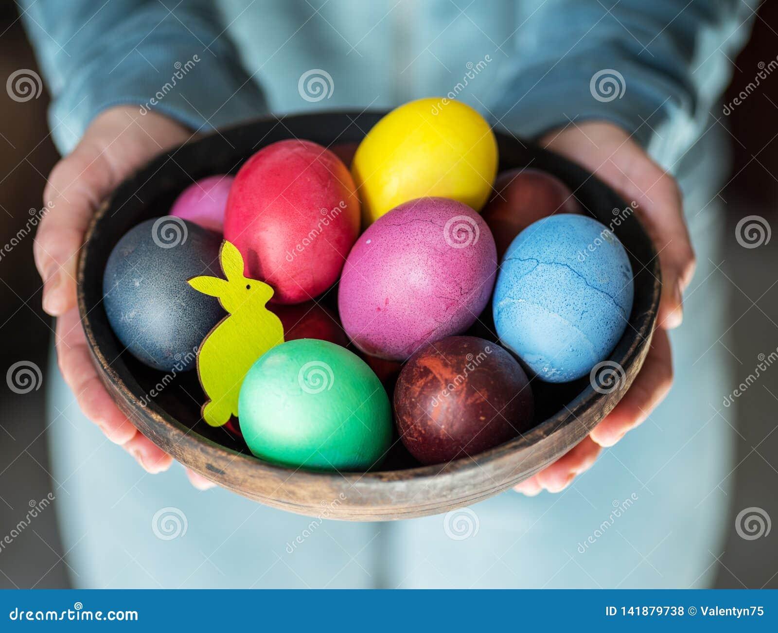 Ζωηρόχρωμα αυγά Πάσχας στο κύπελλο στα χέρια της γυναίκας