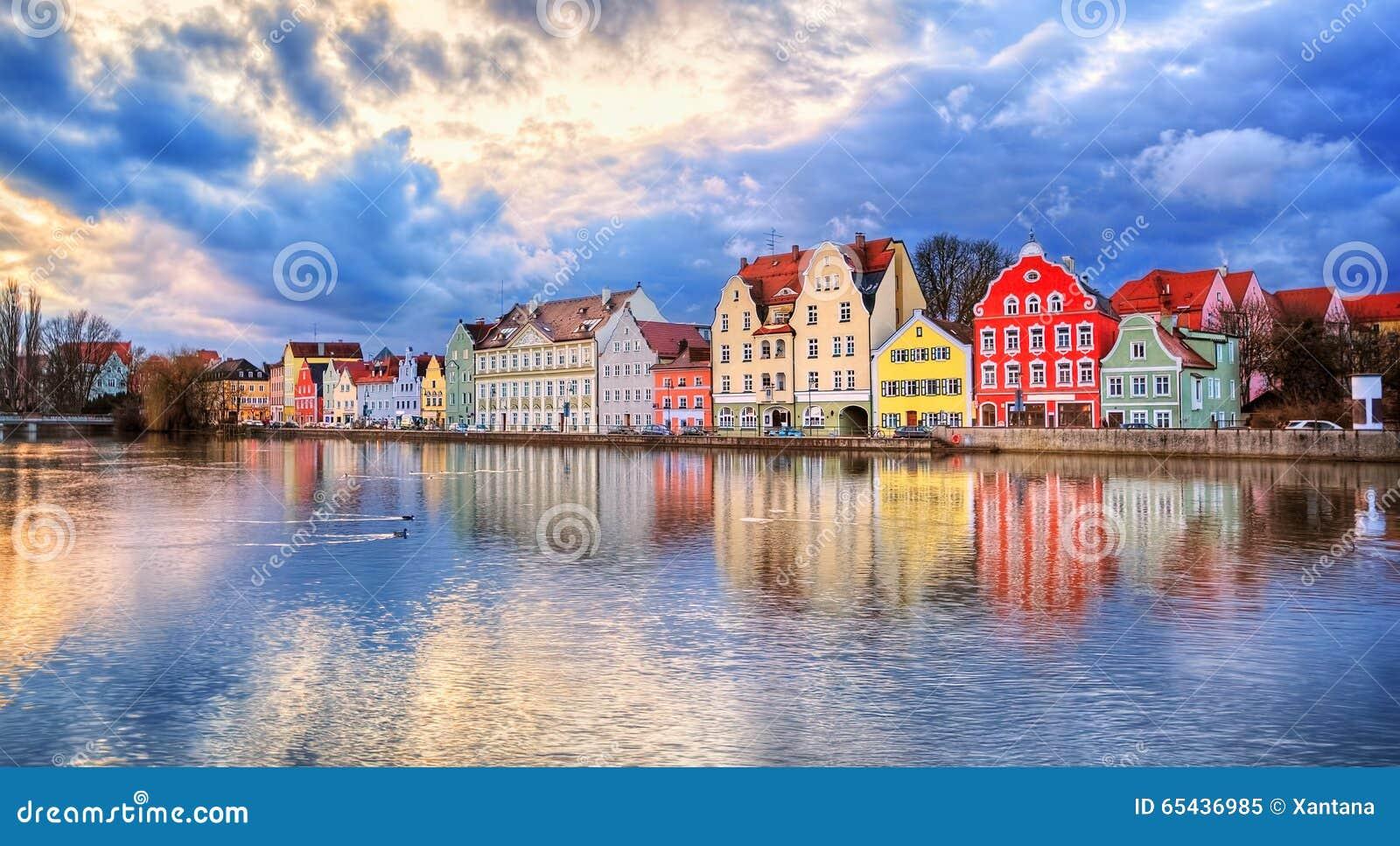 Ζωηρόχρωμα γοτθικά σπίτια που απεικονίζουν Isar στον ποταμό στο ηλιοβασίλεμα, εδάφη