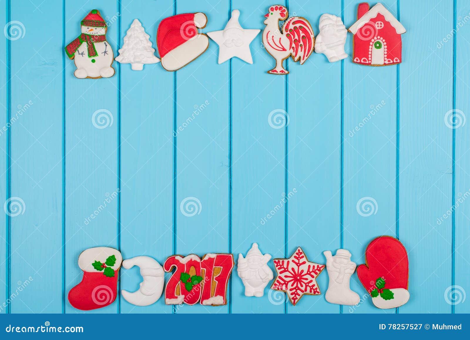 Ζωηρόχρωμα μπισκότα μελοψωμάτων Χριστουγέννων στο μπλε ξύλινο υπόβαθρο