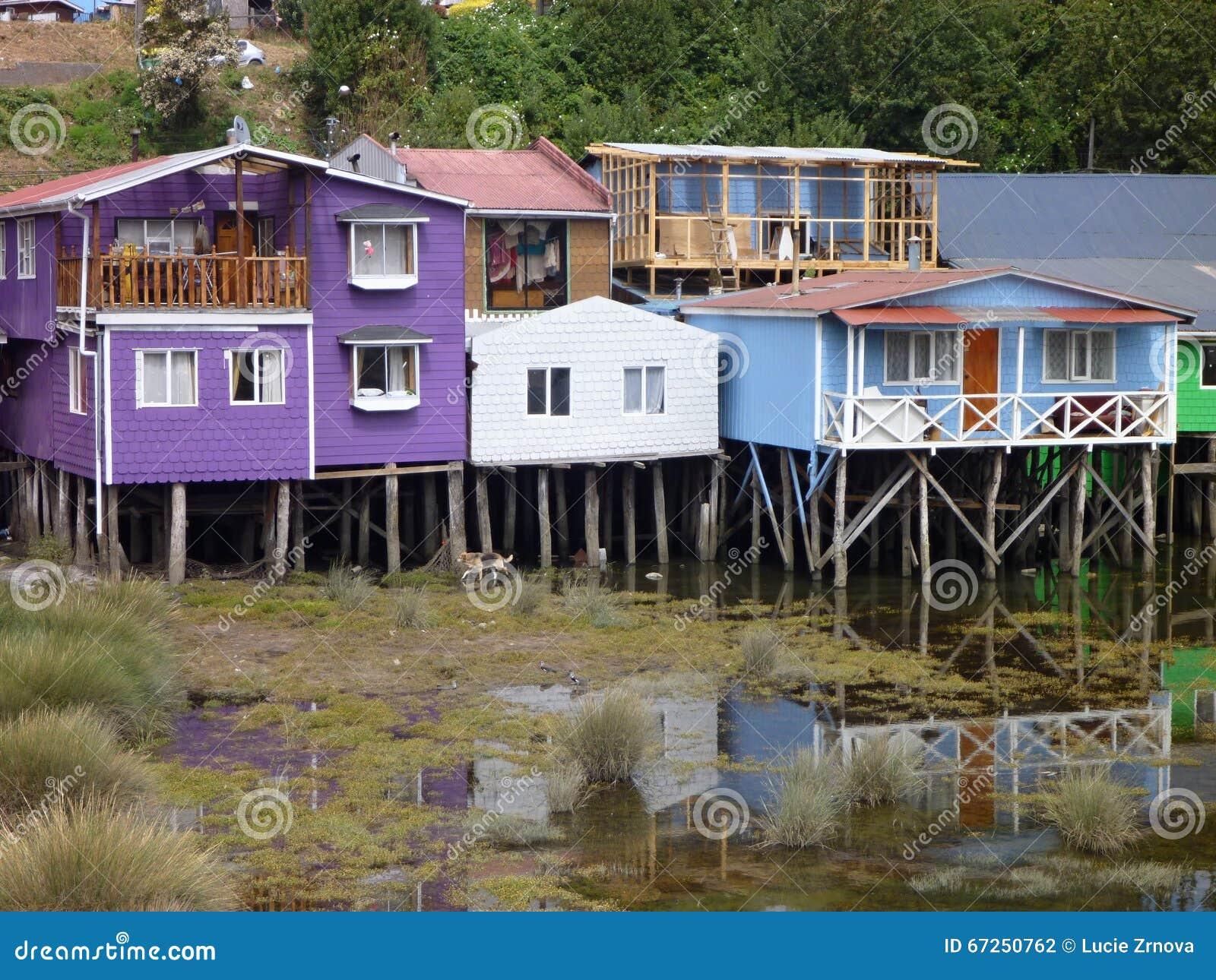Ζωηρόχρωμα σπίτια palafotos στις στήλες woodel στο νησί chiloe