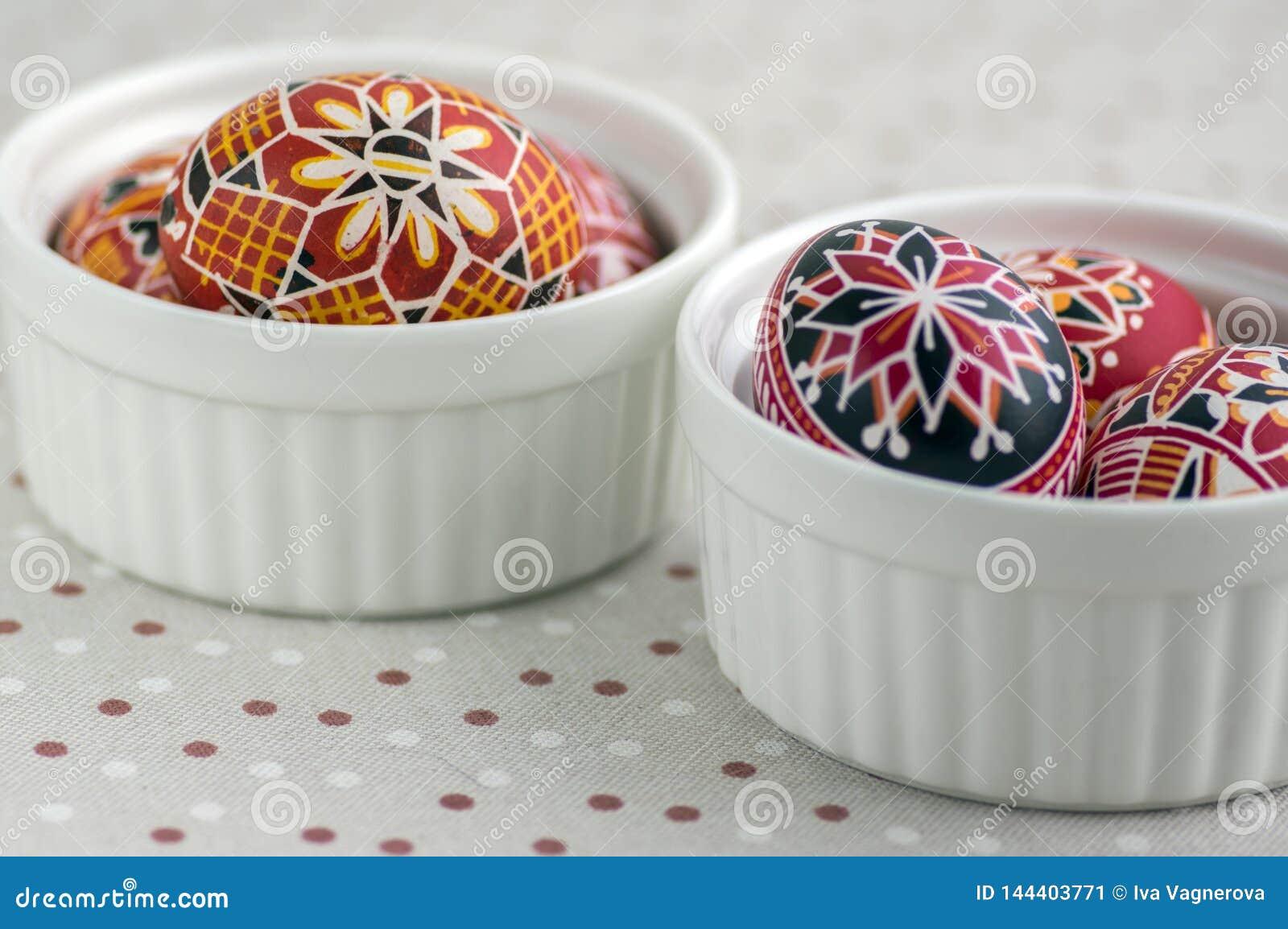 Ζωηρόχρωμα χρωματισμένα αυγά Πάσχας στα άσπρα κύπελλα στο διαστιγμένο τραπεζομάντιλο, παραδοσιακή όμορφη ζωή Πάσχας ακόμα