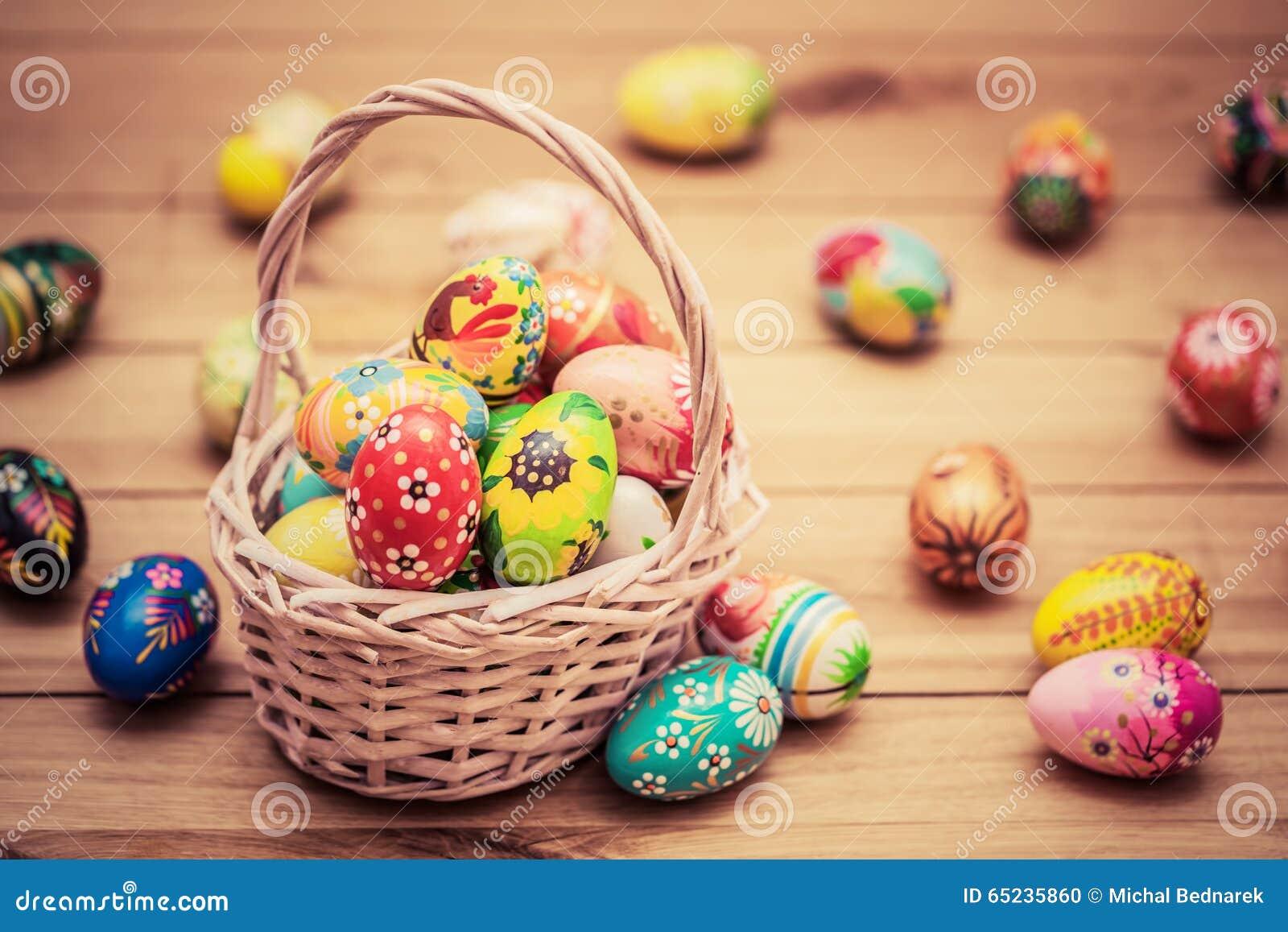 Ζωηρόχρωμα χρωματισμένα χέρι αυγά Πάσχας στο καλάθι και στο ξύλο Χειροποίητη εκλεκτής ποιότητας διακόσμηση