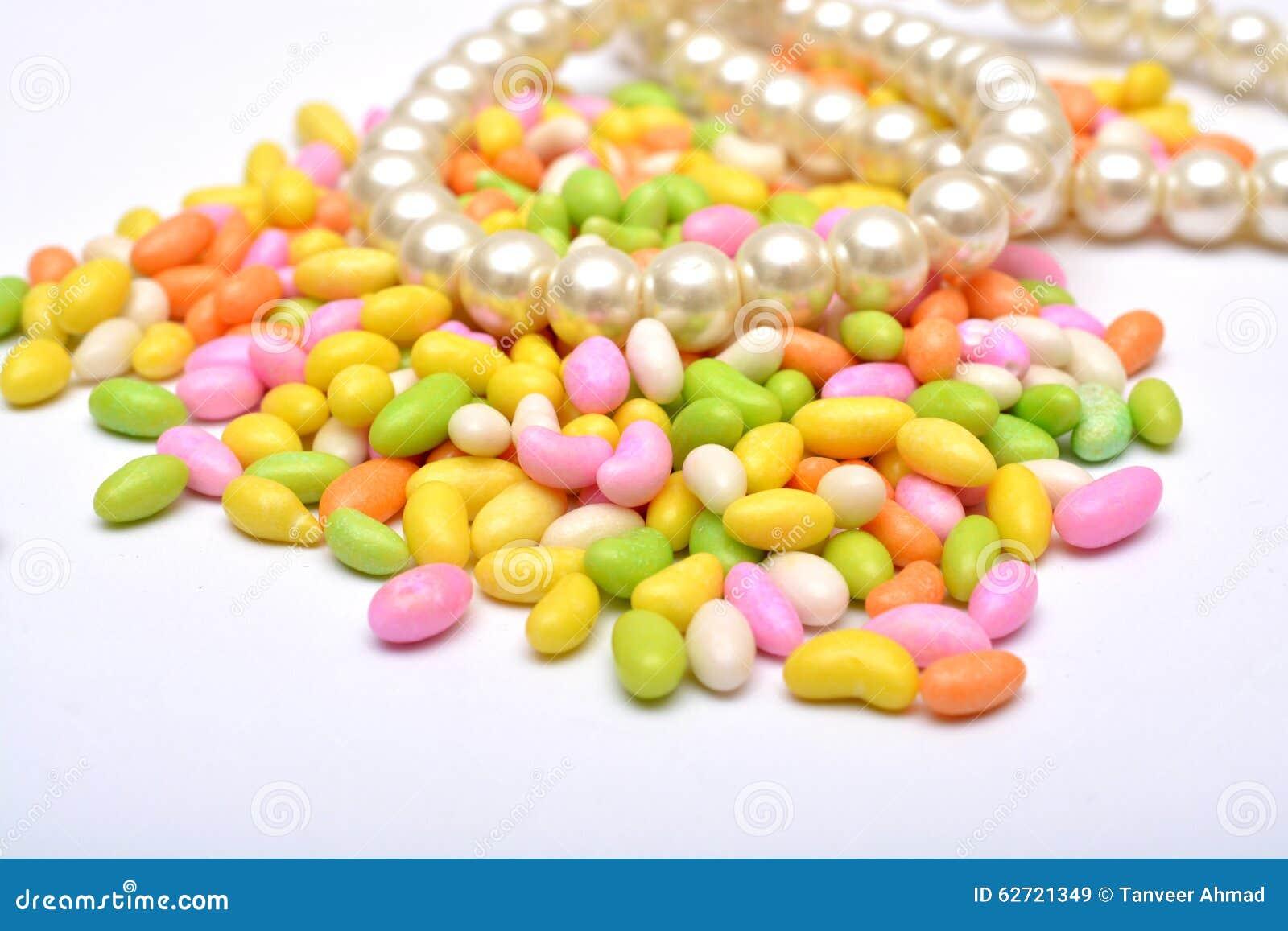 Ζωηρόχρωμες γλυκές καραμέλες με το σχέδιο μαργαριταριών που απομονώνεται