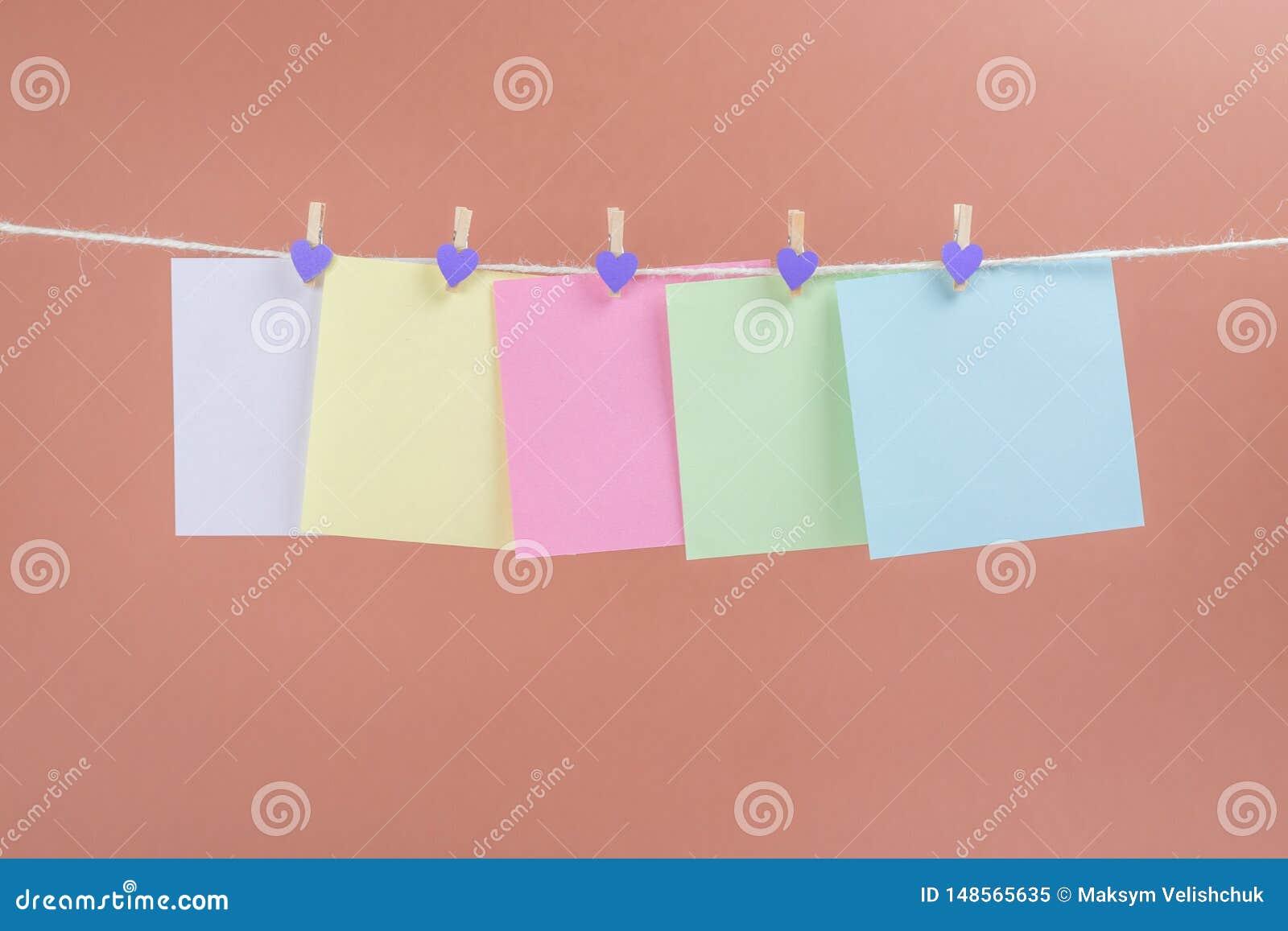Ζωηρόχρωμες κάρτες εγγράφου που κρεμούν το σχοινί που απομονώνεται στο καφετί υπόβαθρο