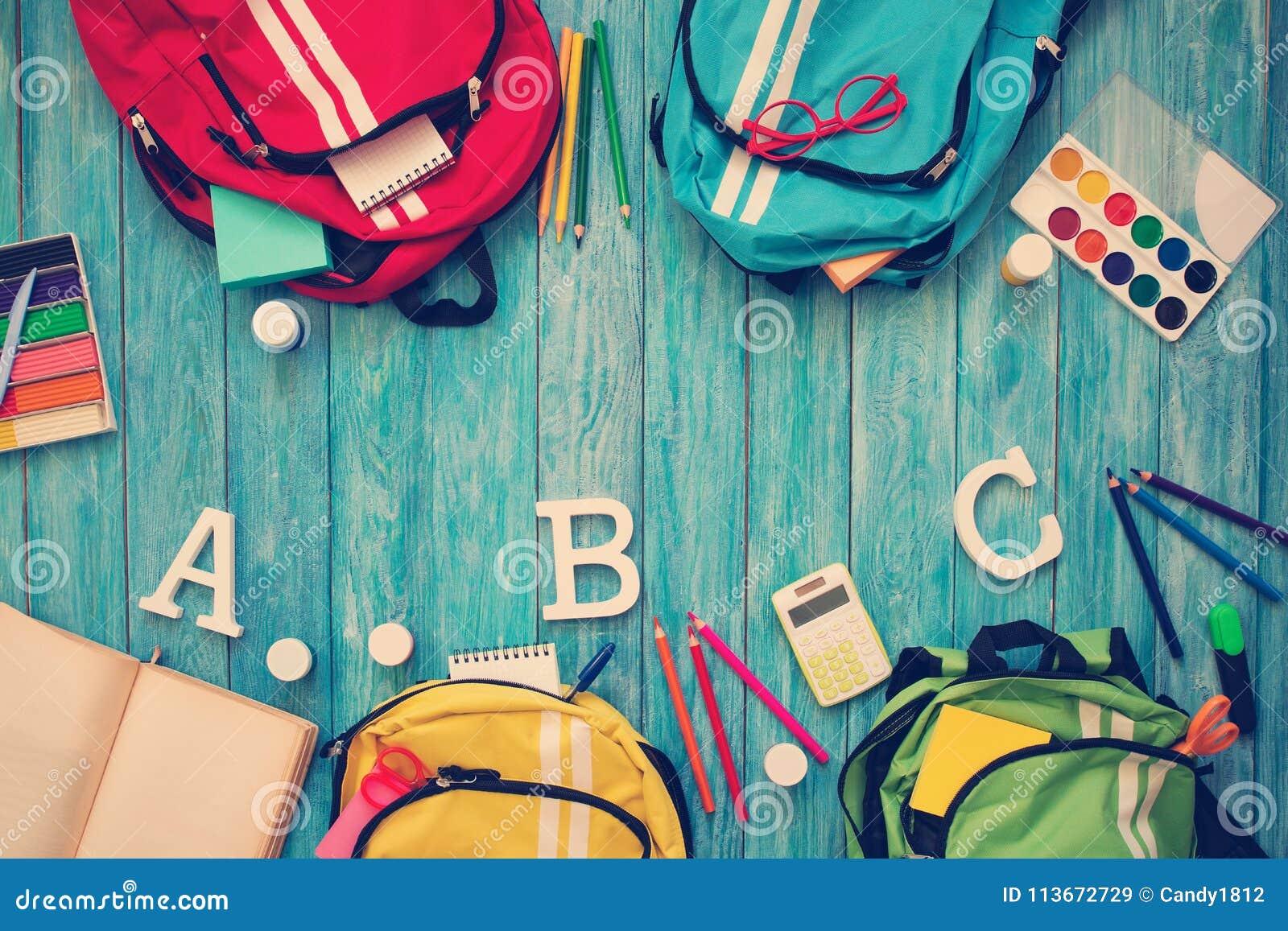 ea474544c92 Ζωηρόχρωμες σχολικές τσάντες παιδιών στο ξύλινο πάτωμα Σακίδια πλάτης με τα  σχολικά εξαρτήματα