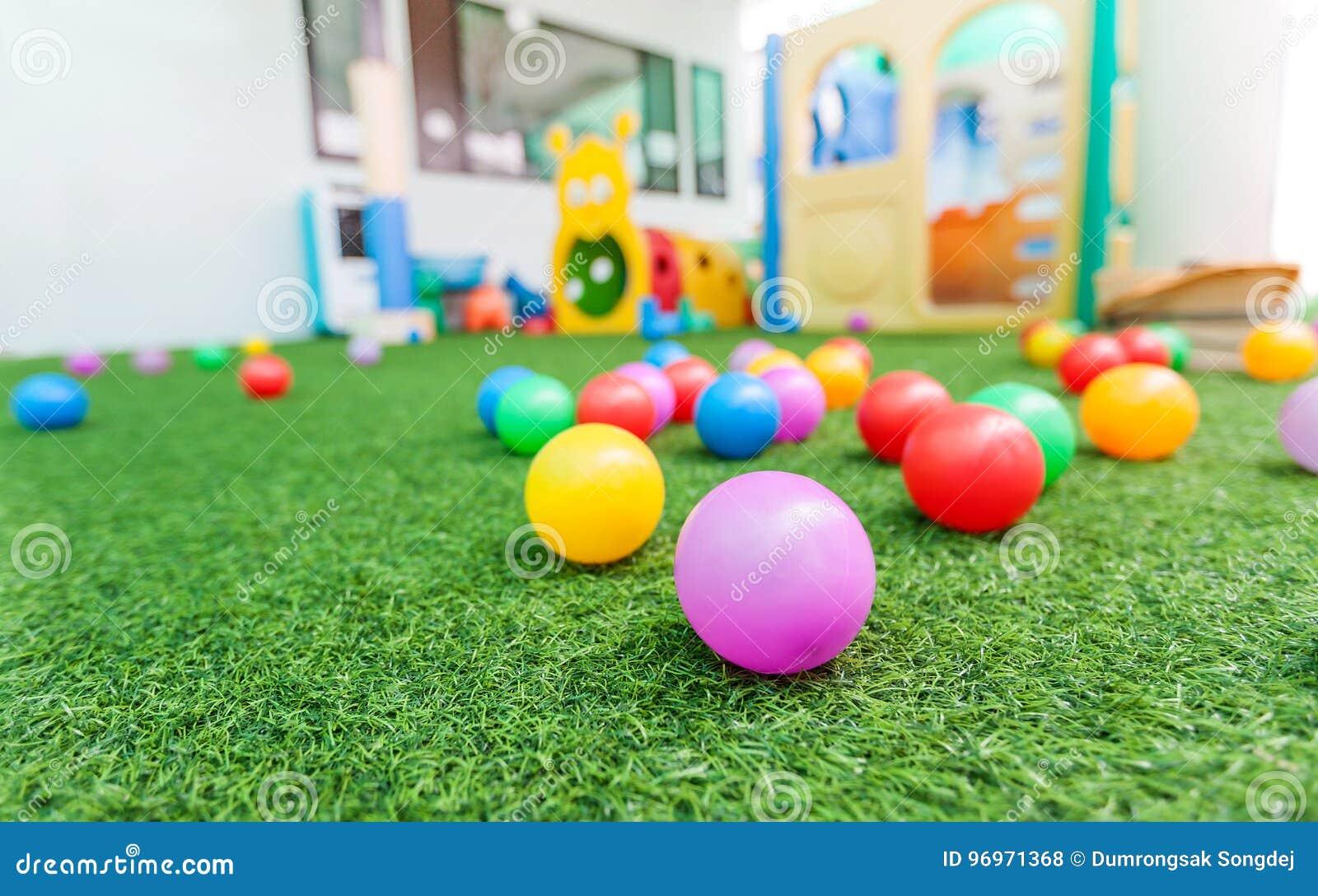 96a7eb518a4 Ζωηρόχρωμη πλαστική σφαίρα στην πράσινη τύρφη στη σχολική παιδική ...