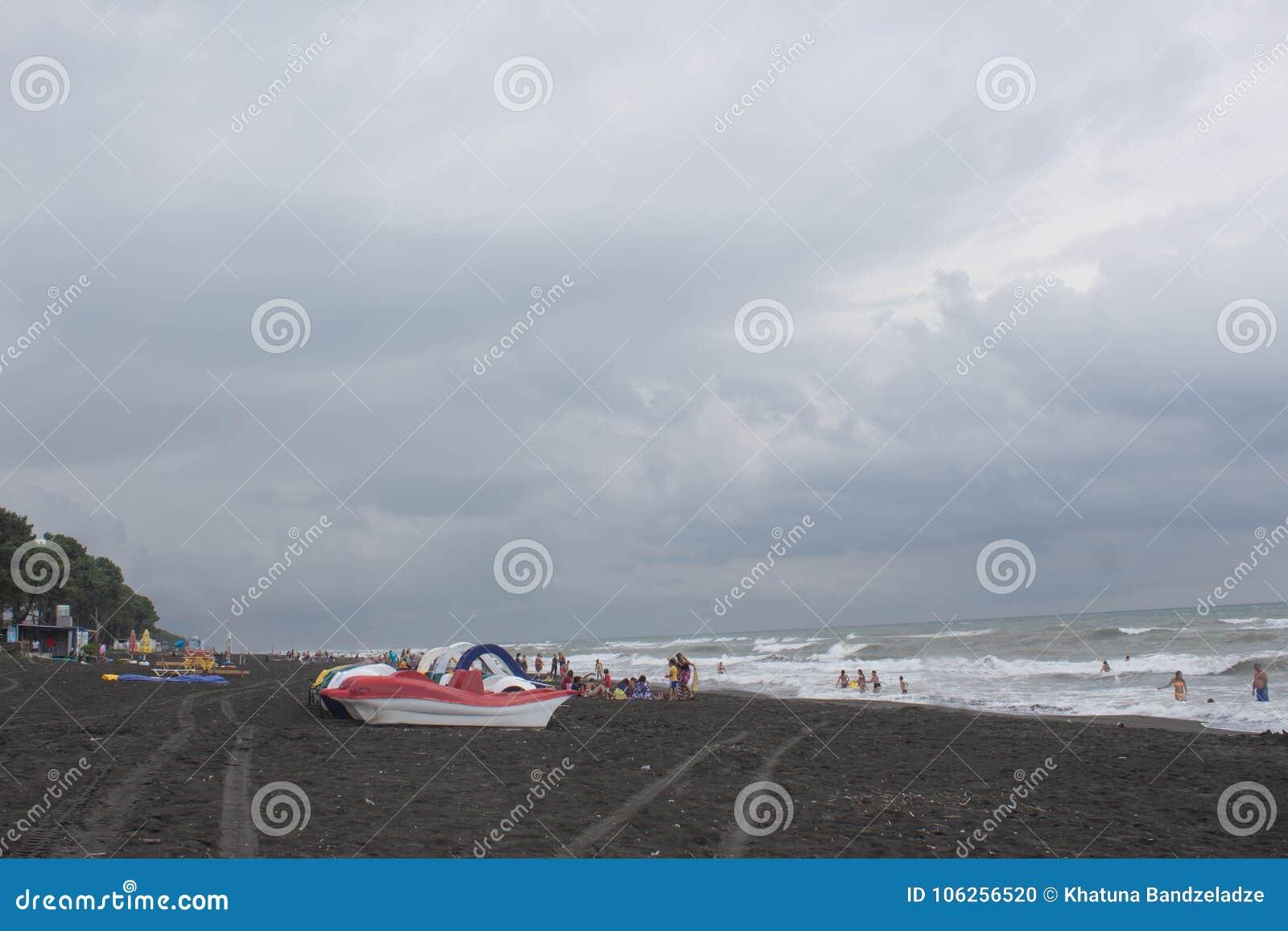 Ζωηρόχρωμη σειρά pedalo που σταθμεύουν στην παραλία, συννεφιασμένος, σύννεφα, κύματα