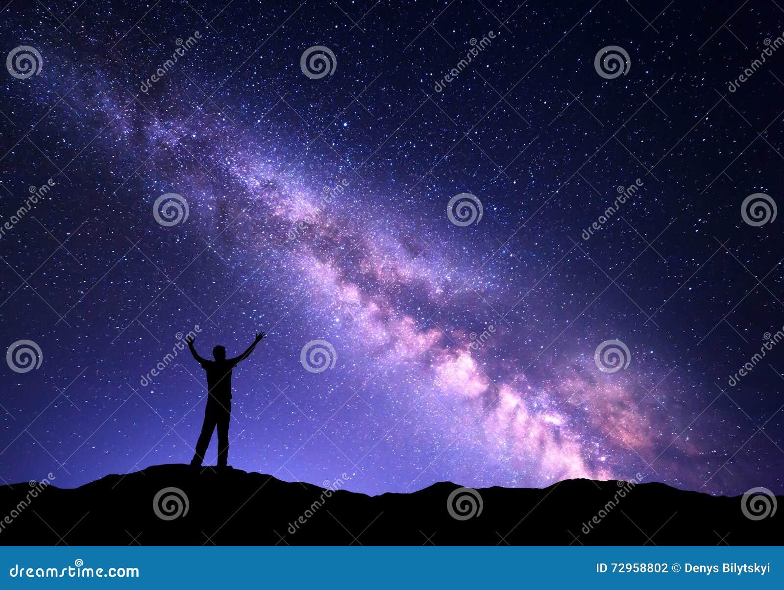 Ζωηρόχρωμο τοπίο νύχτας με τον πορφυρούς γαλακτώδεις τρόπο και τη σκιαγραφία ενός μόνιμου φίλαθλου ατόμου με αυξημένος επάνω στα