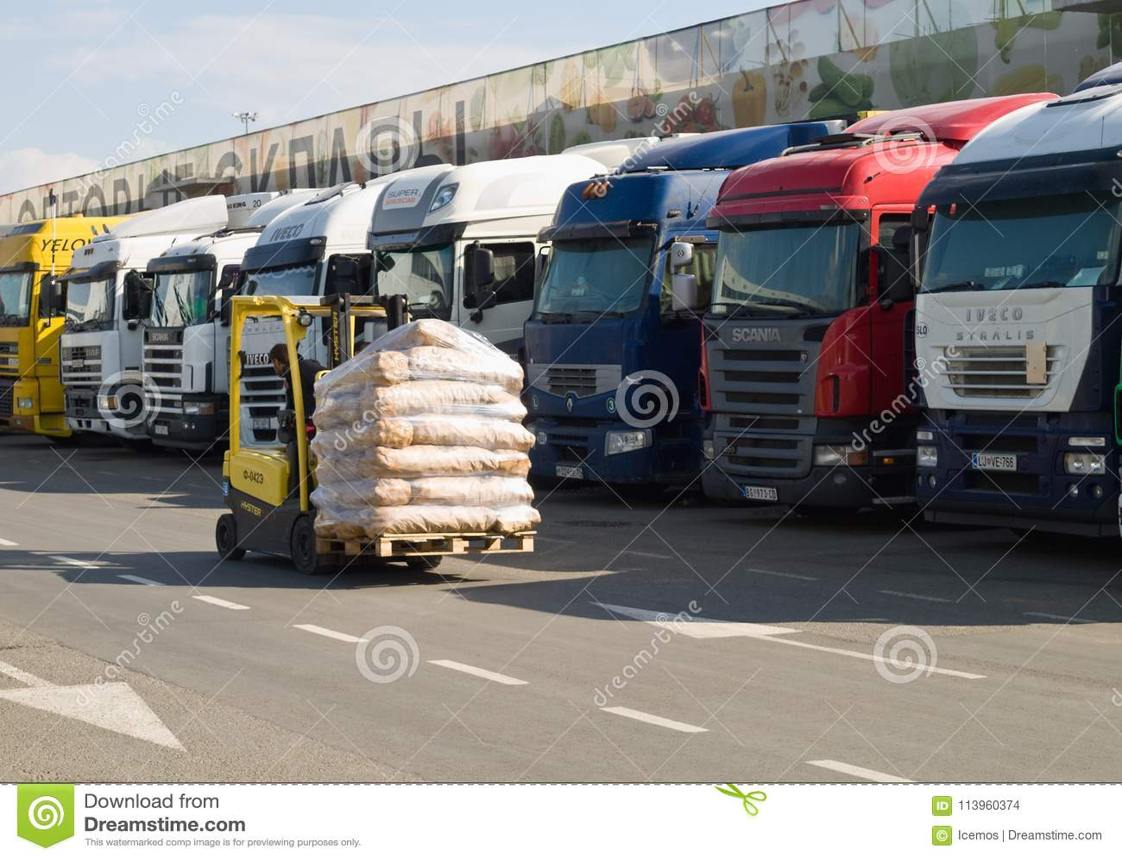 Ηλεκτρικό forklift με το φορτίο στο υπόβαθρο μιας μακροχρόνιας σειράς φορτηγών που στέκονται στην εκφόρτωση στην αποθήκη εμπορευμ