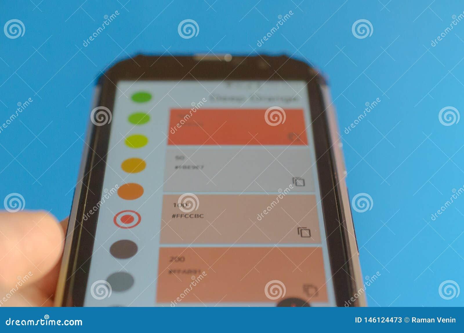 Ηλεκτρονικές παλέτες χρώματος μεταξύ του smartphone και του μπλε υποβάθρου