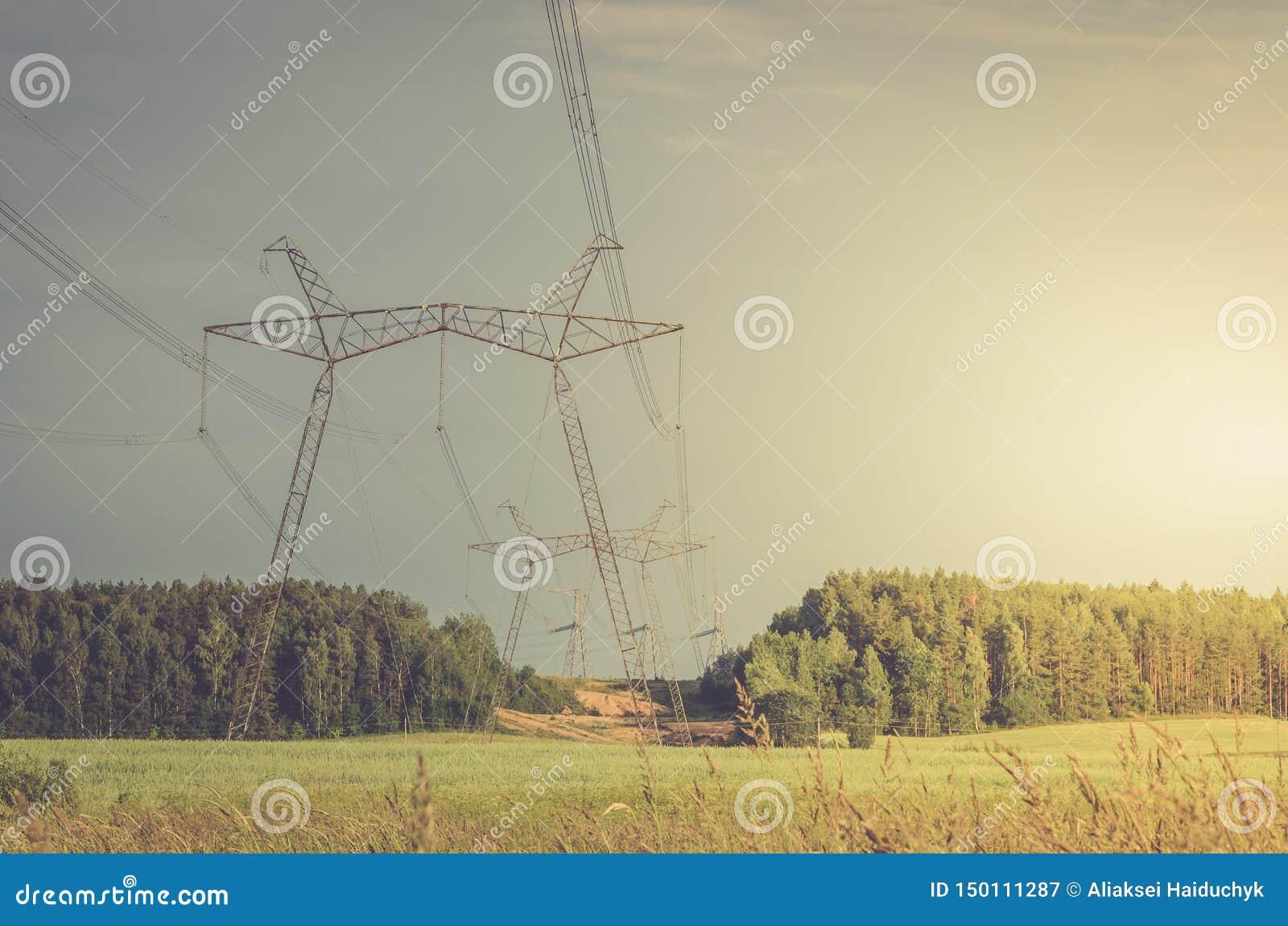 Ηλεκτρο πύργοι υψηλής τάσης/ηλεκτρο πύργοι υψηλής τάσης ενάντια σε ένα επάνω ηλιοβασίλεμα υποβάθρου