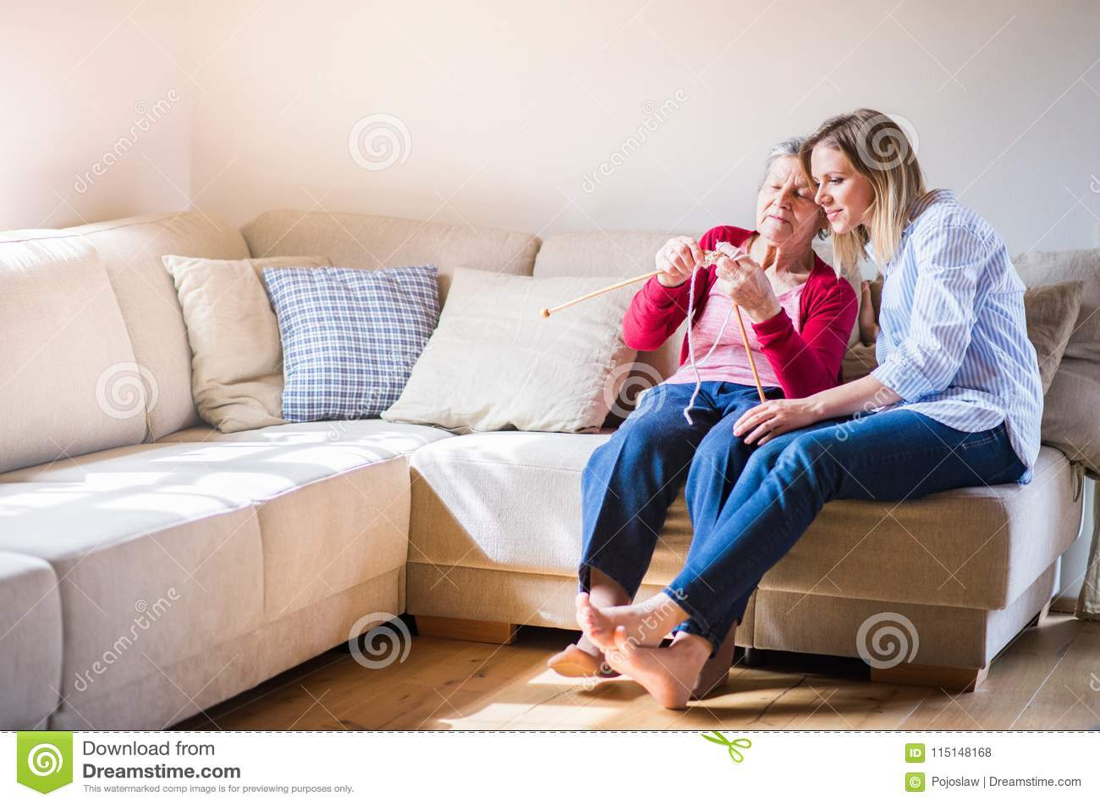 Ηλικιωμένη γιαγιά και ενήλικη εγγονή στο σπίτι, πλέξιμο